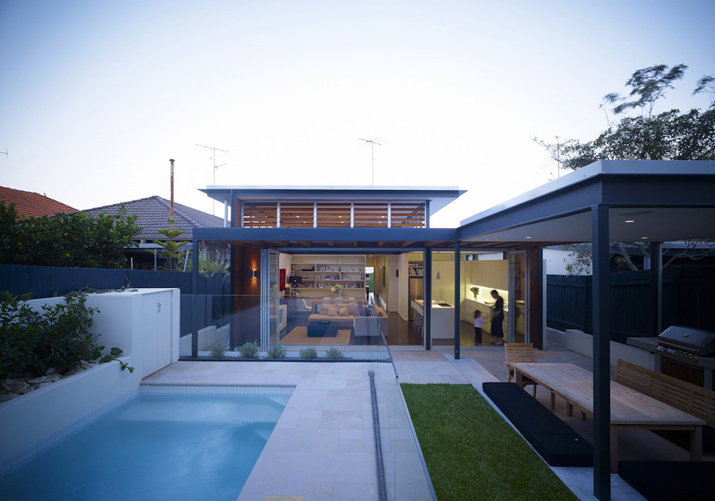 Lambert House by Sydney award winning residential architecture office Sam Crawford Architects. View to western facade from backyard with pool and outdoor barbecue.