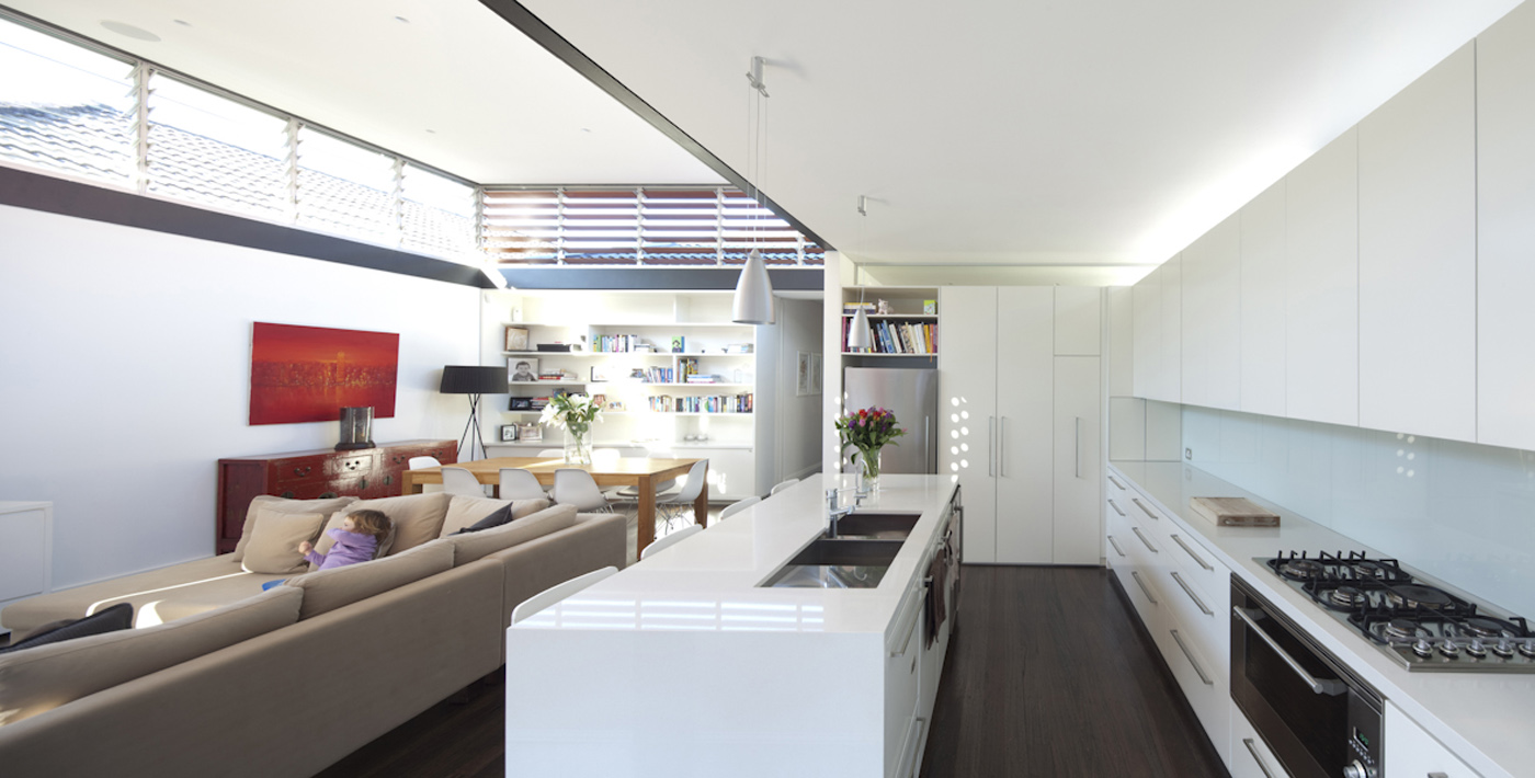 Lambert House by Sydney award winning residential architecture office Sam Crawford Architects. Long narrow kitchen connected to living space with glass louver windows allow sunlight and ventilation