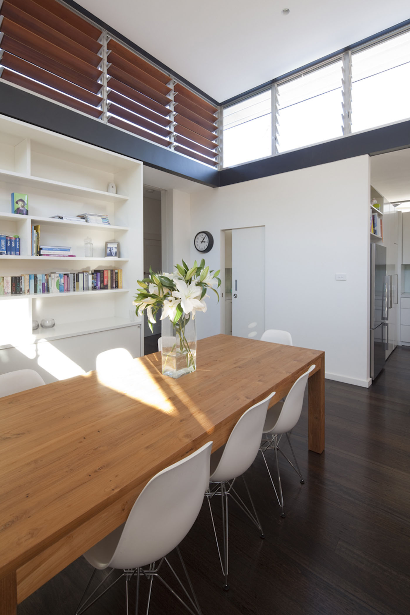 Lambert House by Sydney award winning residential architecture office Sam Crawford Architects. Light filled dining room with timber and glass louvers.