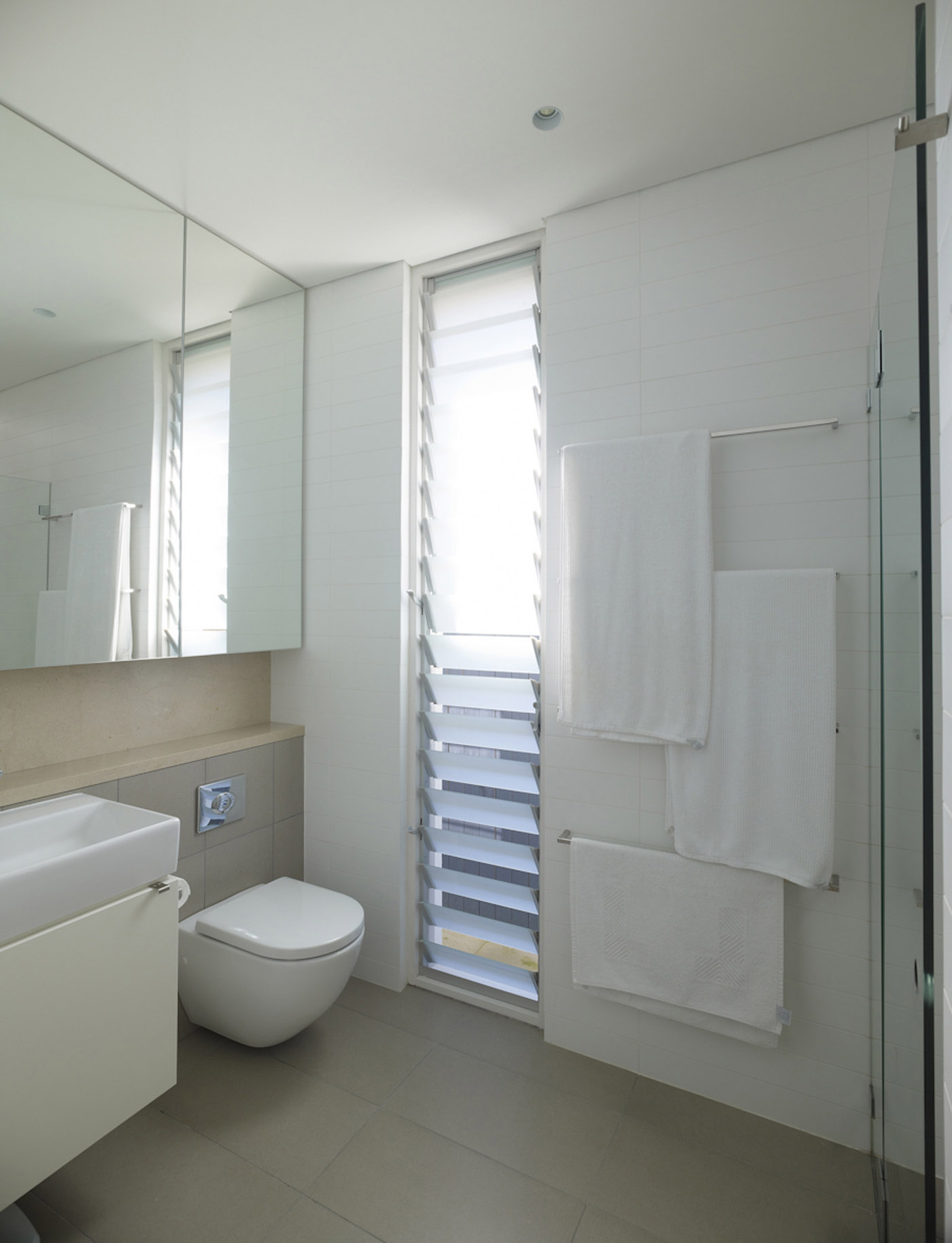 Lambert House by Sydney award winning residential architecture office Sam Crawford Architects. Light brown and white tiled bathroom.