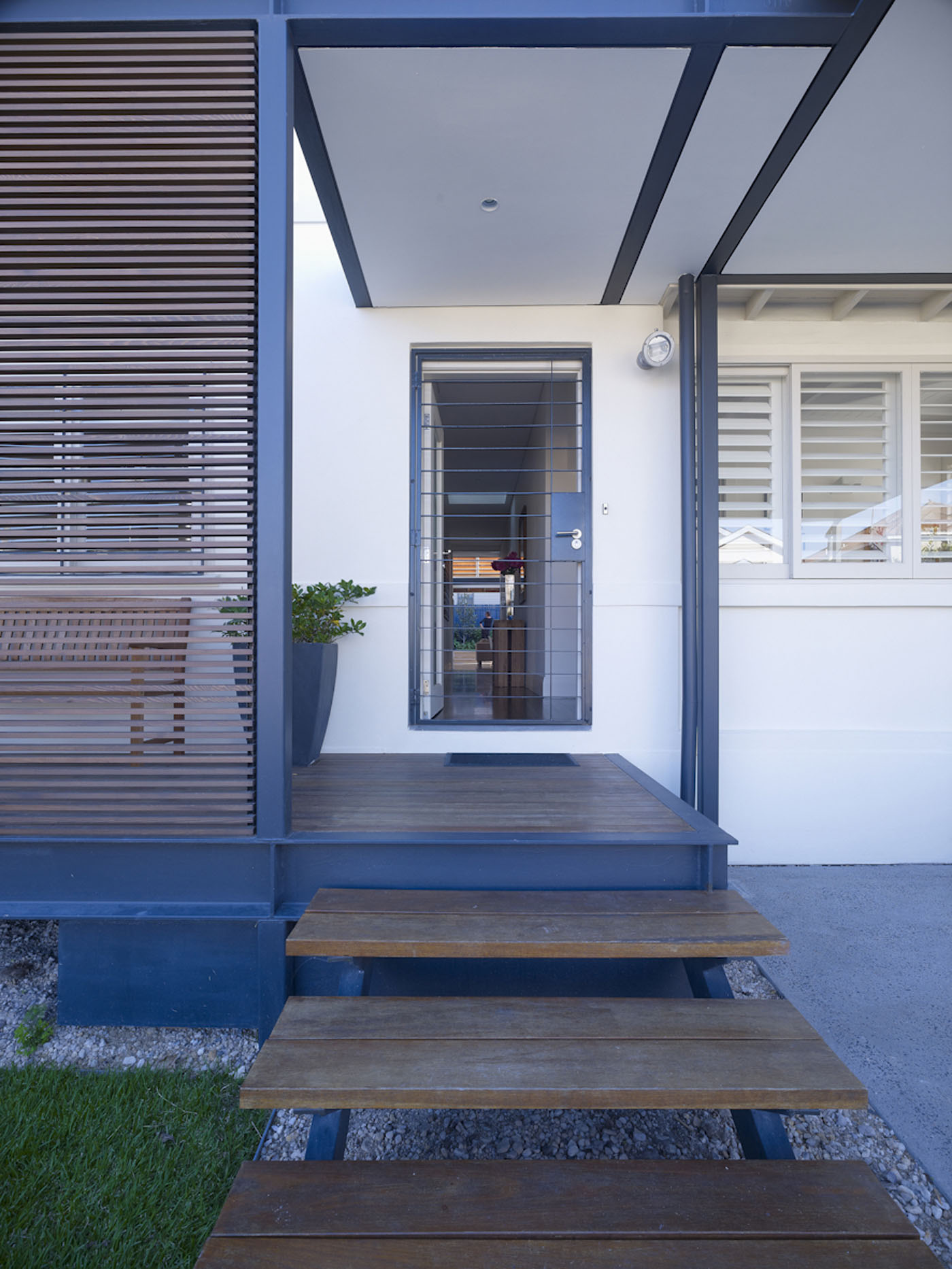 Lambert House by Sydney award winning residential architecture office Sam Crawford Architects. Spotted gum timber board decking with covered pergola at front entry.