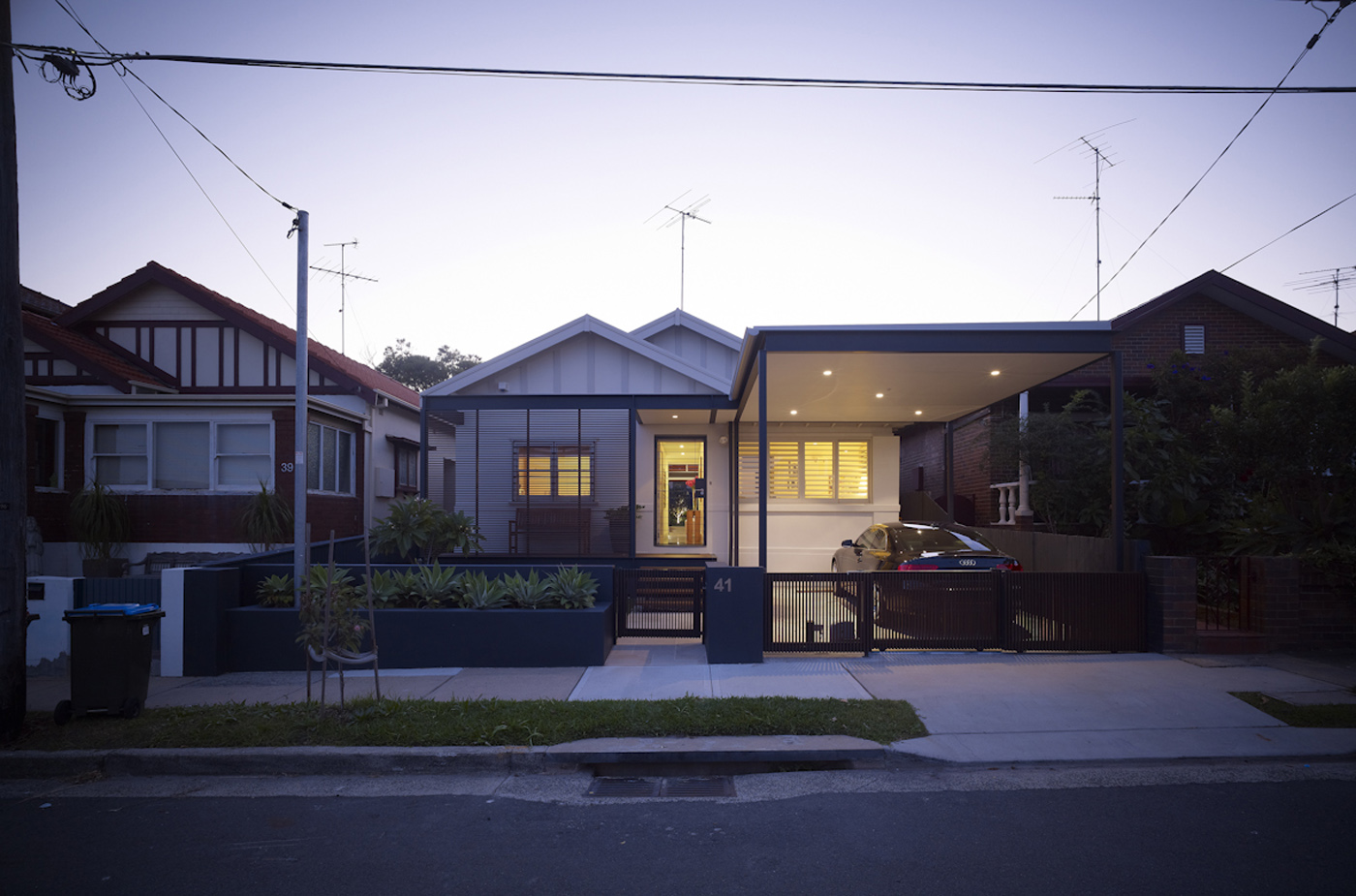 Lambert House by Sydney award winning residential architecture office Sam Crawford Architects. View to front entry at twilight