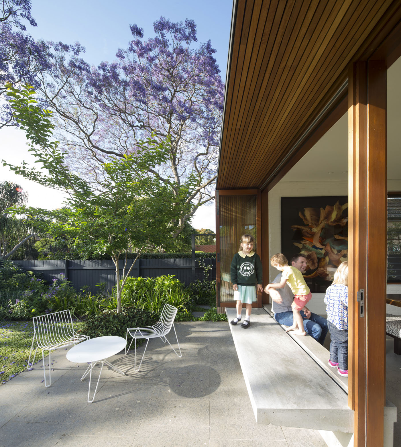 Denney House by Sam Crawford Architects, children having fun on the window seat connecting to the garden