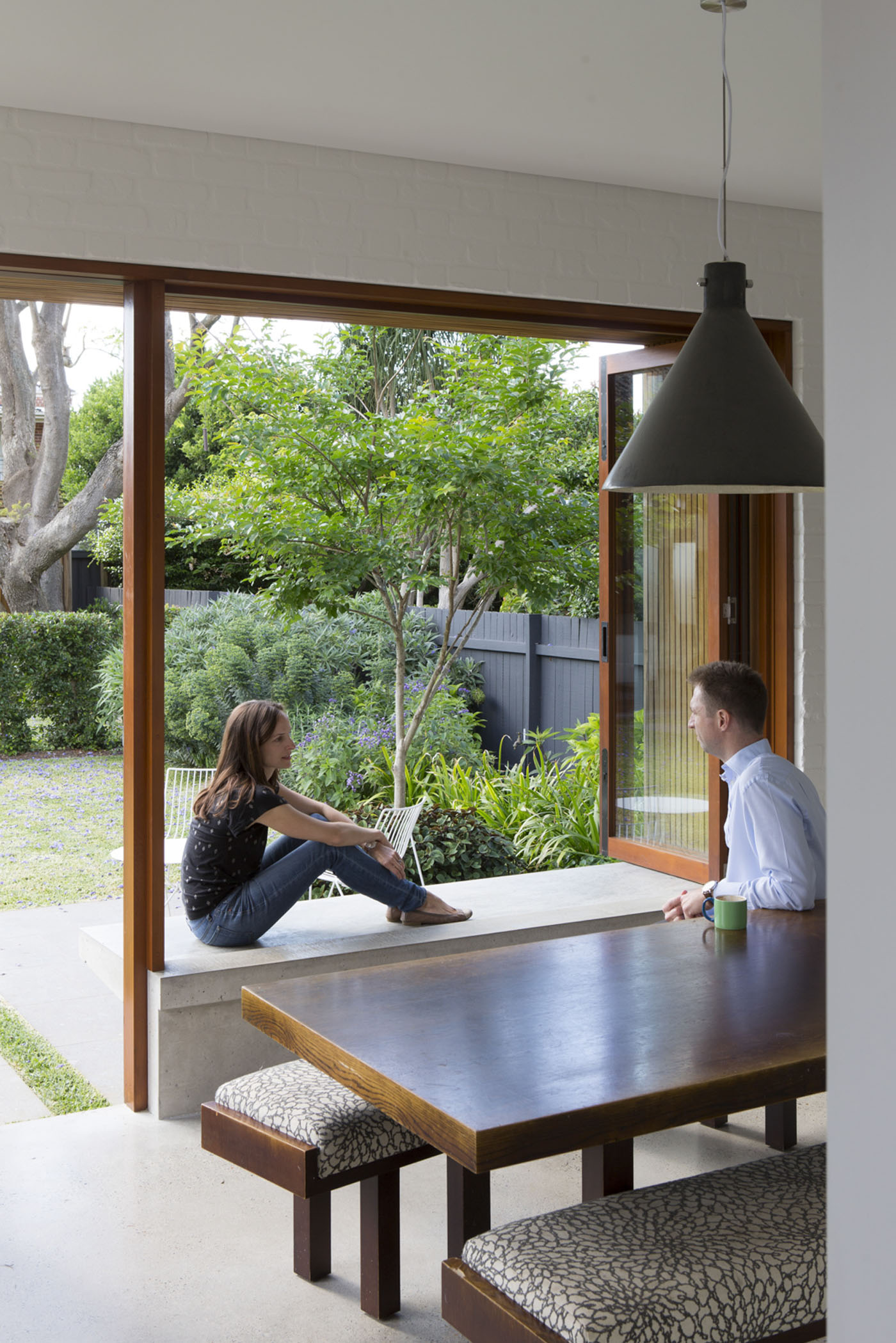 Denney House by Sam Crawford Architects, two people enjoying a chat in the open space between the dining room and the garden