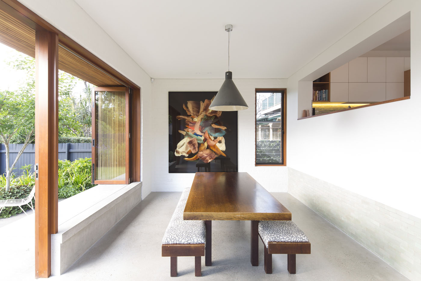 Denney House by Sam Crawford Architects, view to solid timber dining table with large pendant and feature artwork