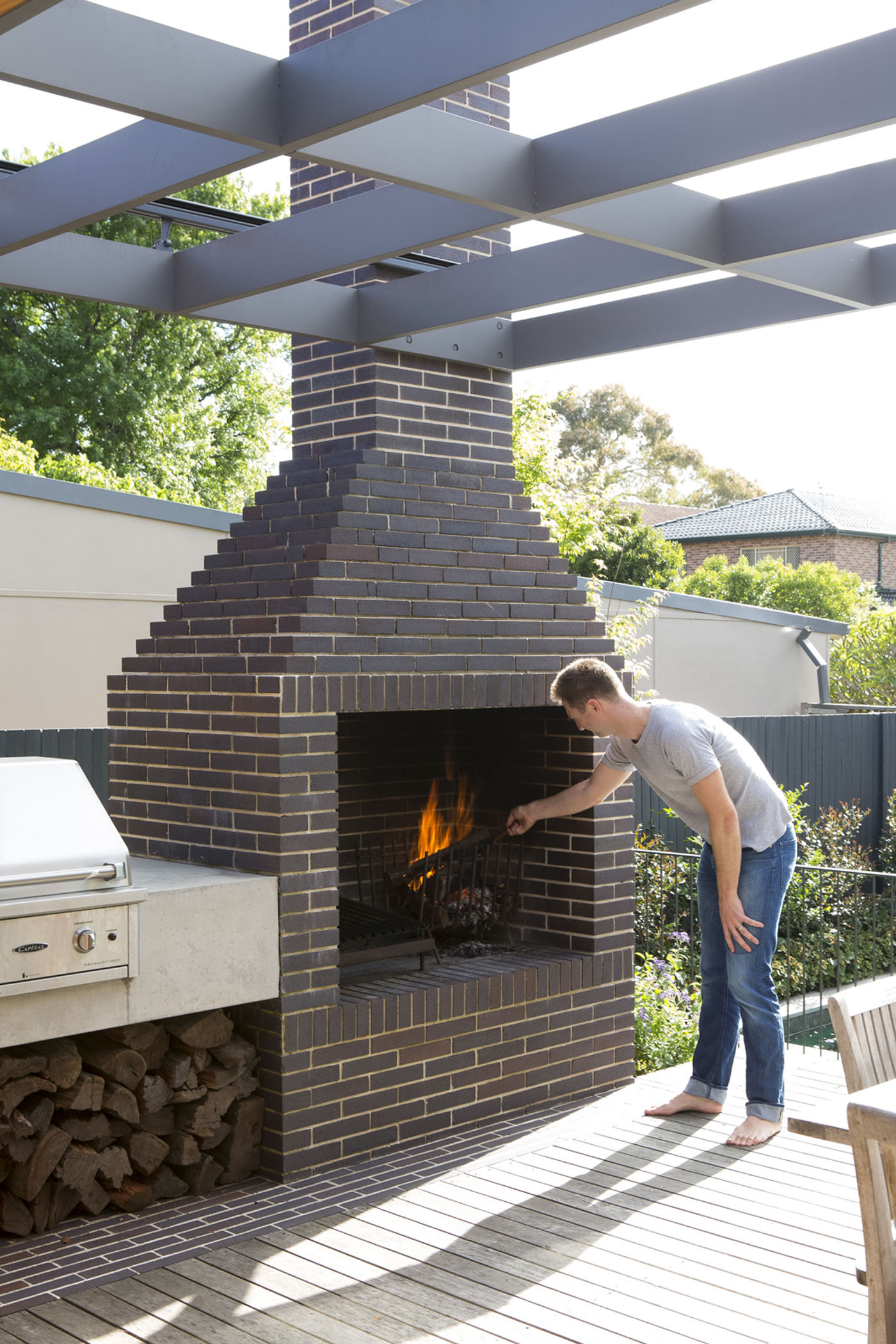 Denney House by Sam Crawford Architects, outdoor brick fireplace connected to barbecue area