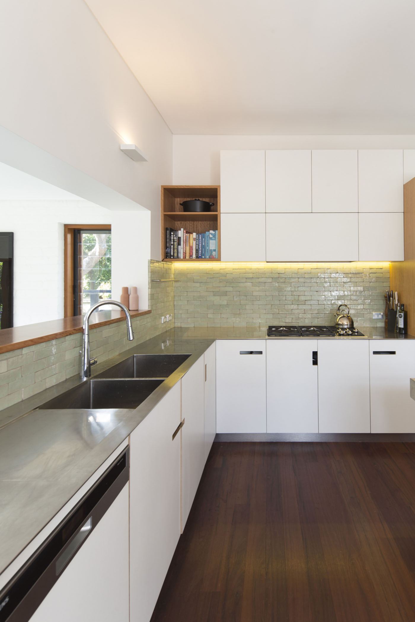 Denney House by Sam Crawford Architects, stainless steel benchtop kitchen with tiled splashback and custom cupboard handles