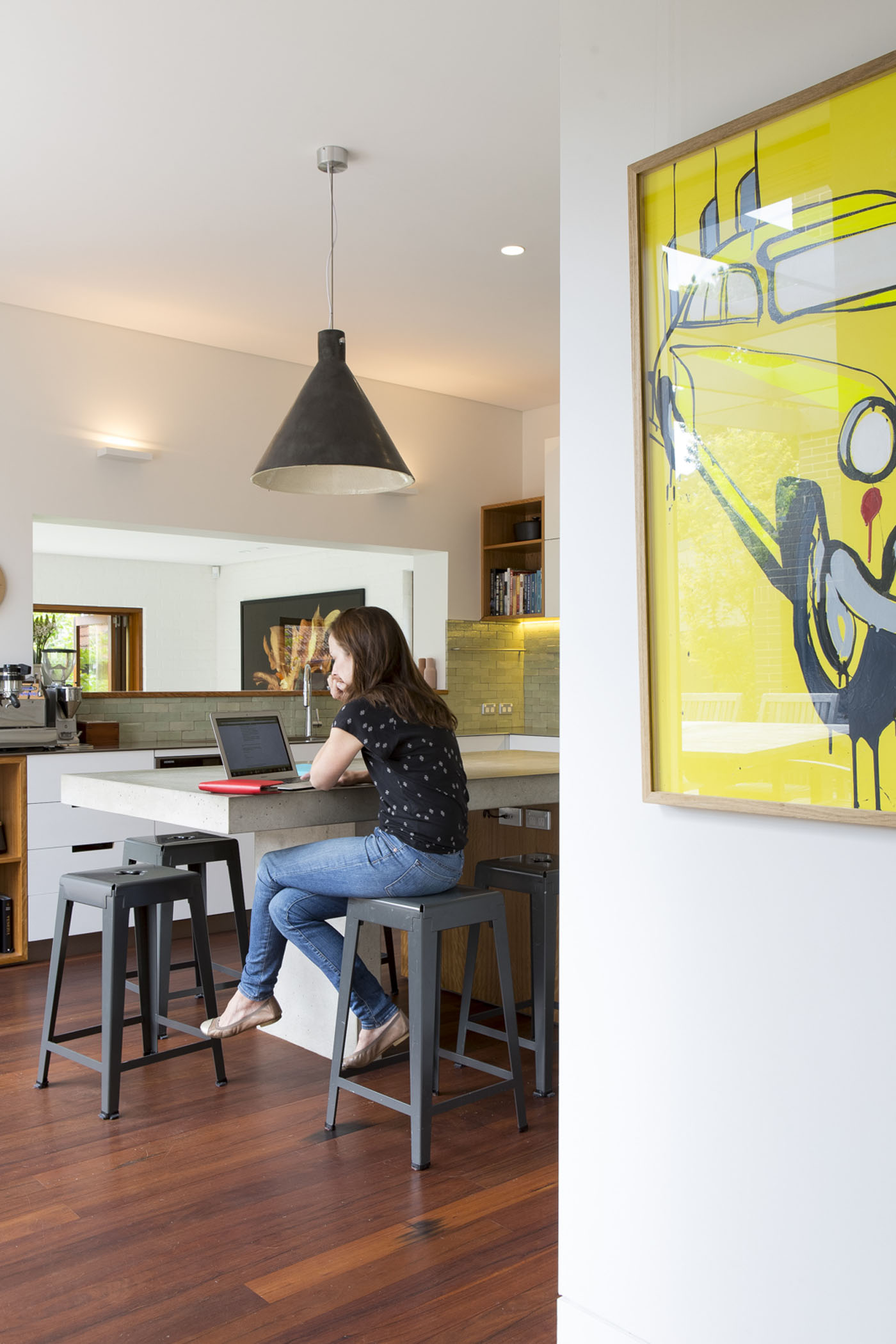 Denney House by Sam Crawford Architects, kitchen featuring concrete island with large feature pendant and charcoal stools
