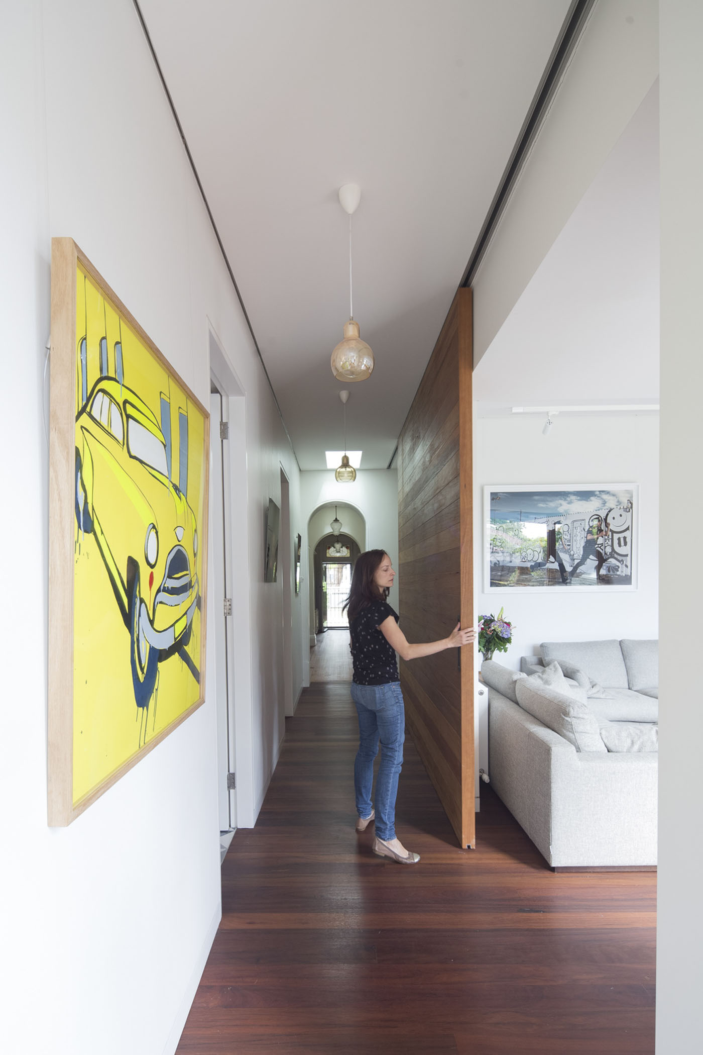 Denney House by Sam Crawford Architects, woman standing in hallway and moving full height timber door