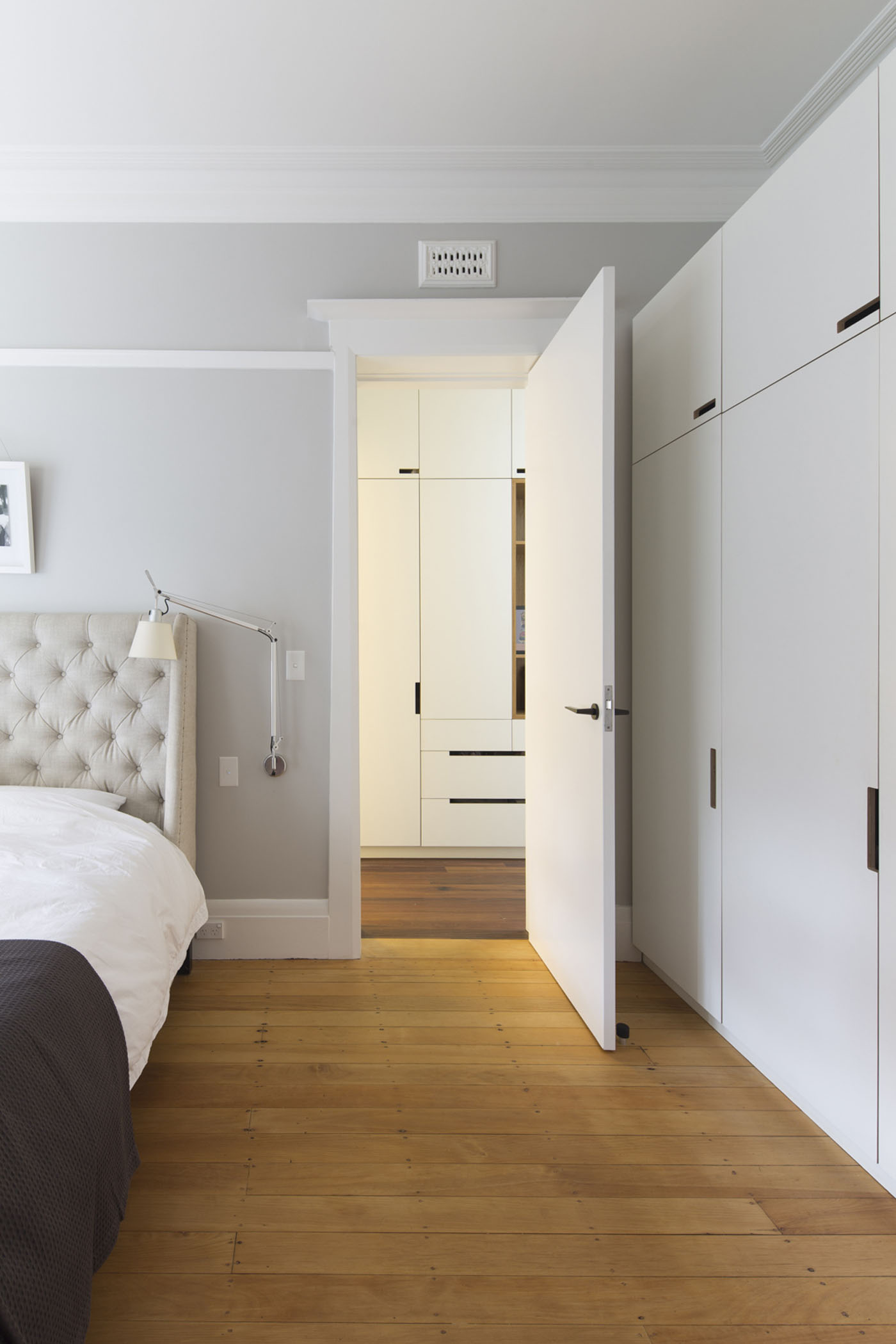 Denney House by Sam Crawford Architects, bedroom with wooden plank floor and subtle wall colour