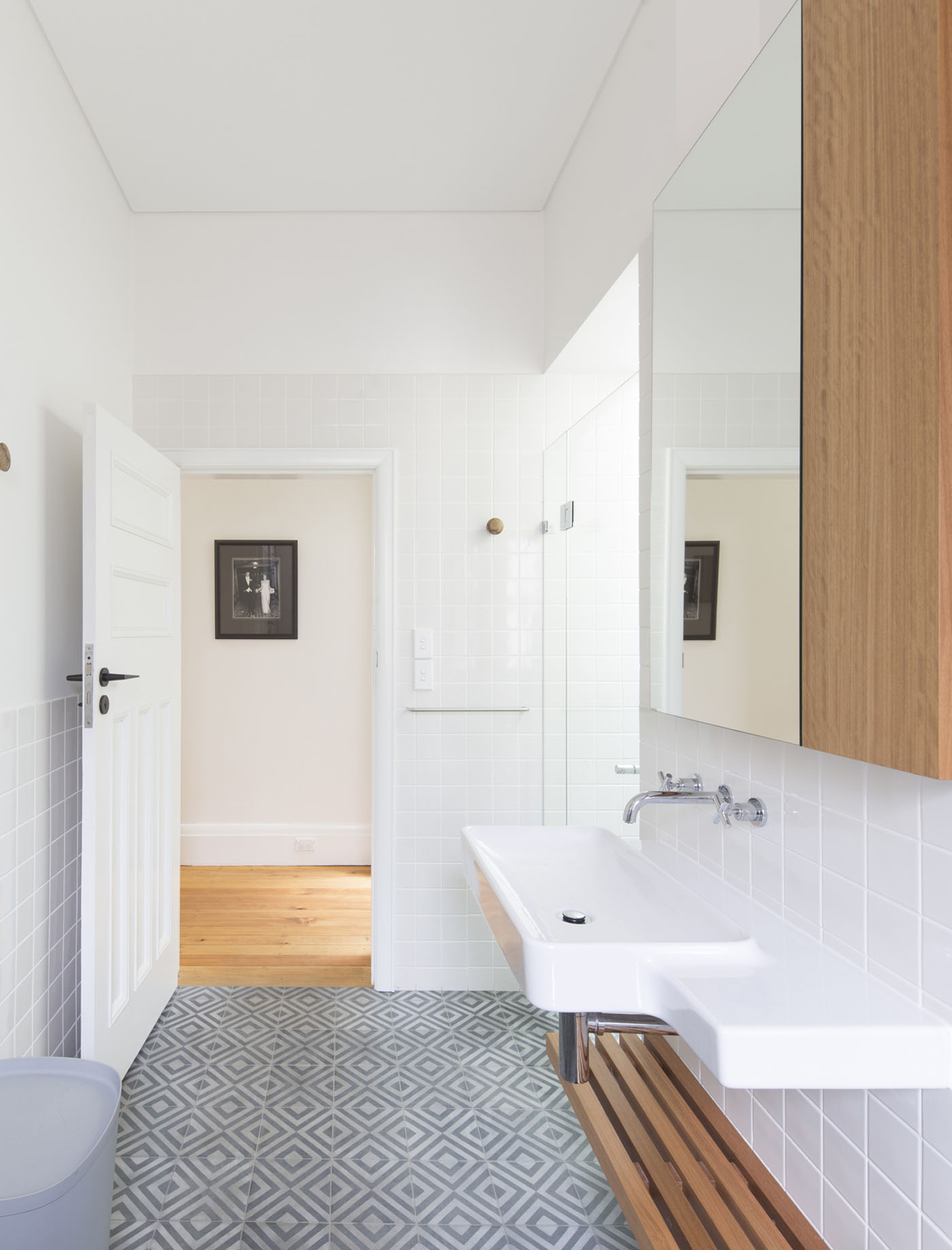 Denney House by Sam Crawford Architects, bathroom featuring popham diamond floor tiles, square gloss white tile and slatted timber shelf