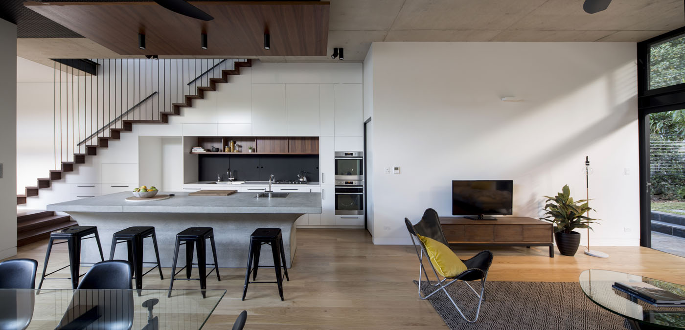Sheppard Wilson House by Sydney award winning residential architecture office Sam Crawford Architects. Bespoke kitchen and living area featuring concrete bench