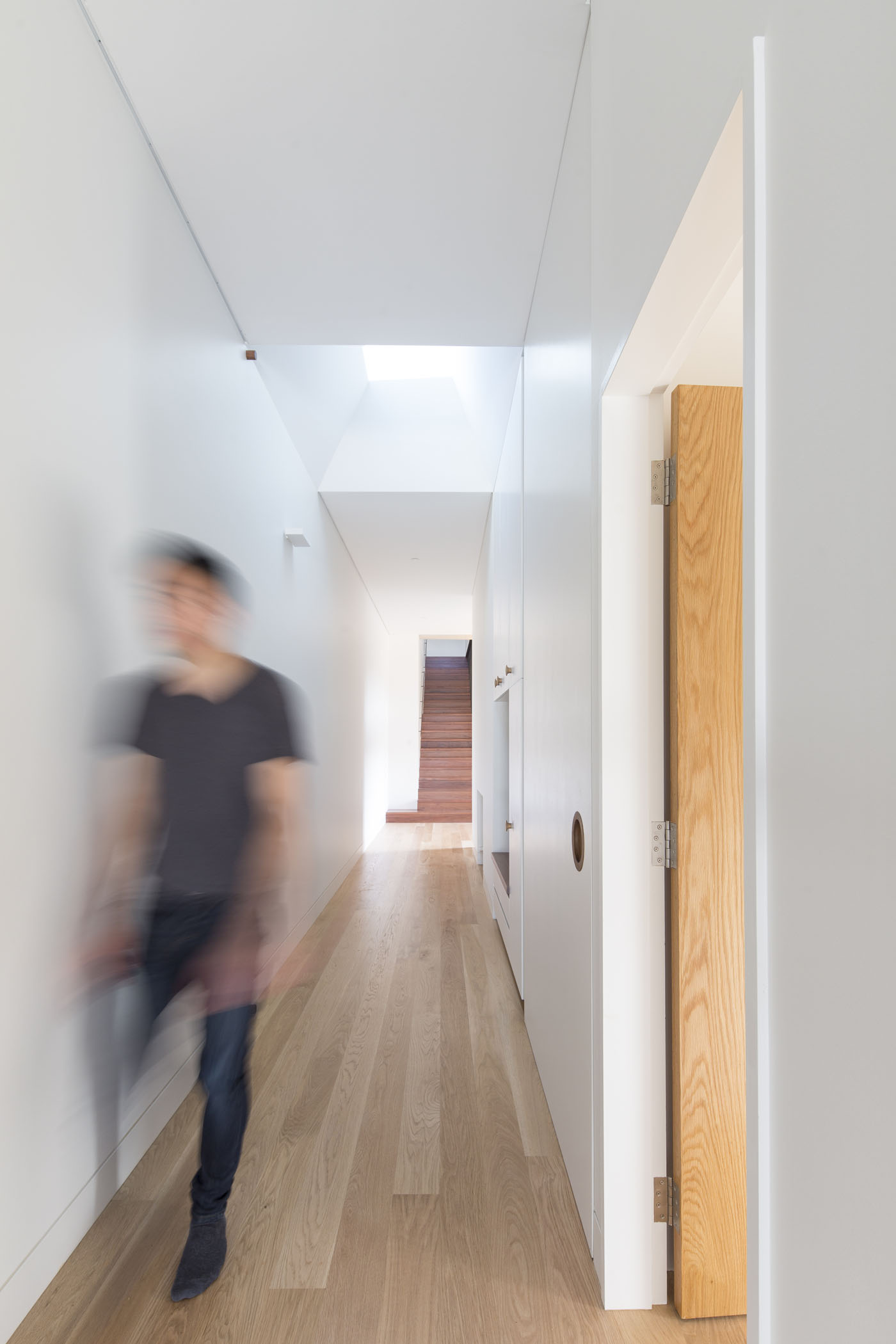 Sheppard Wilson House by Sydney award winning residential architecture office Sam Crawford Architects. Angled skylight allow sunlight into corridor