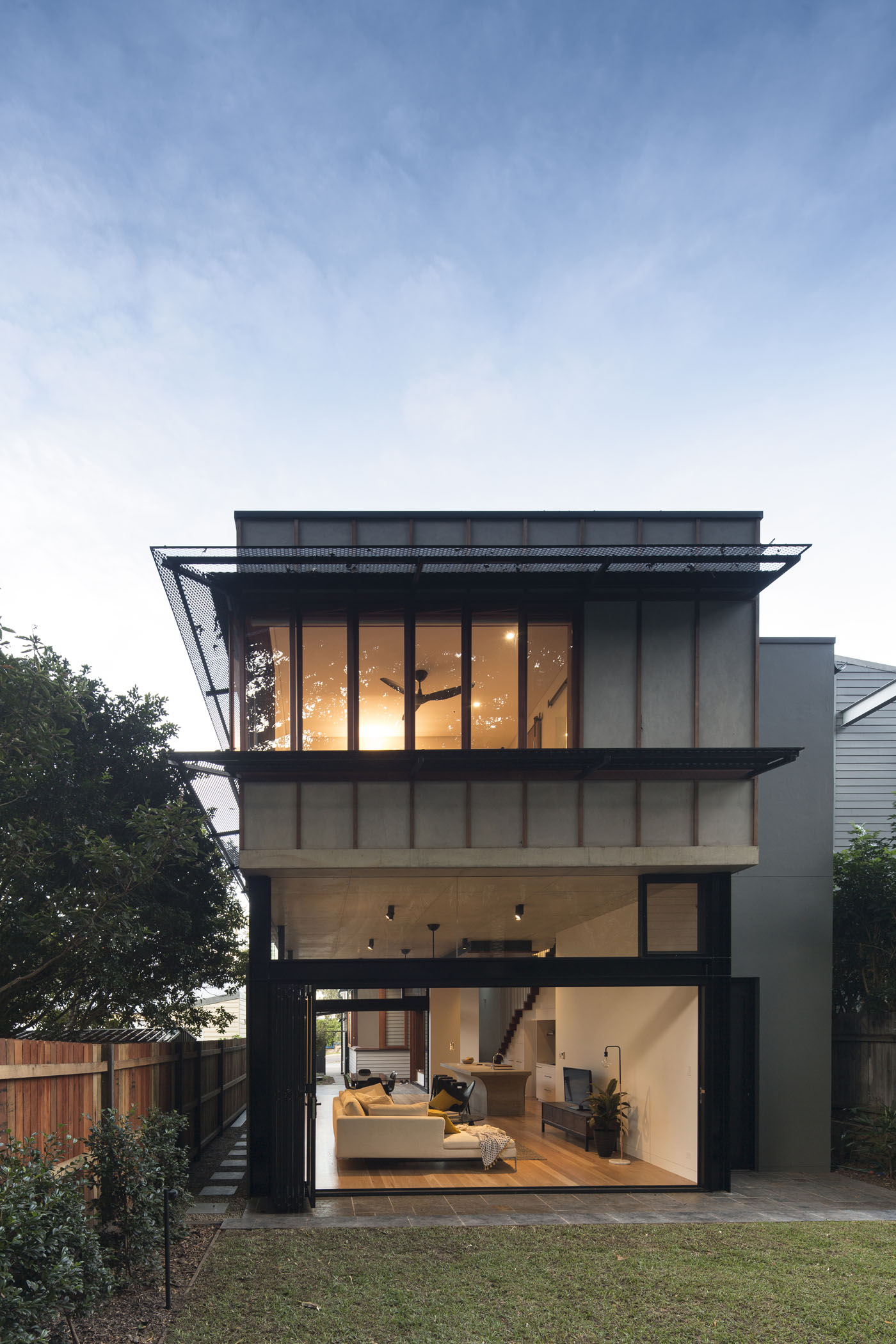 Sheppard Wilson House by Sydney award winning residential architecture office Sam Crawford Architects. Western facade looking into living room at twilight