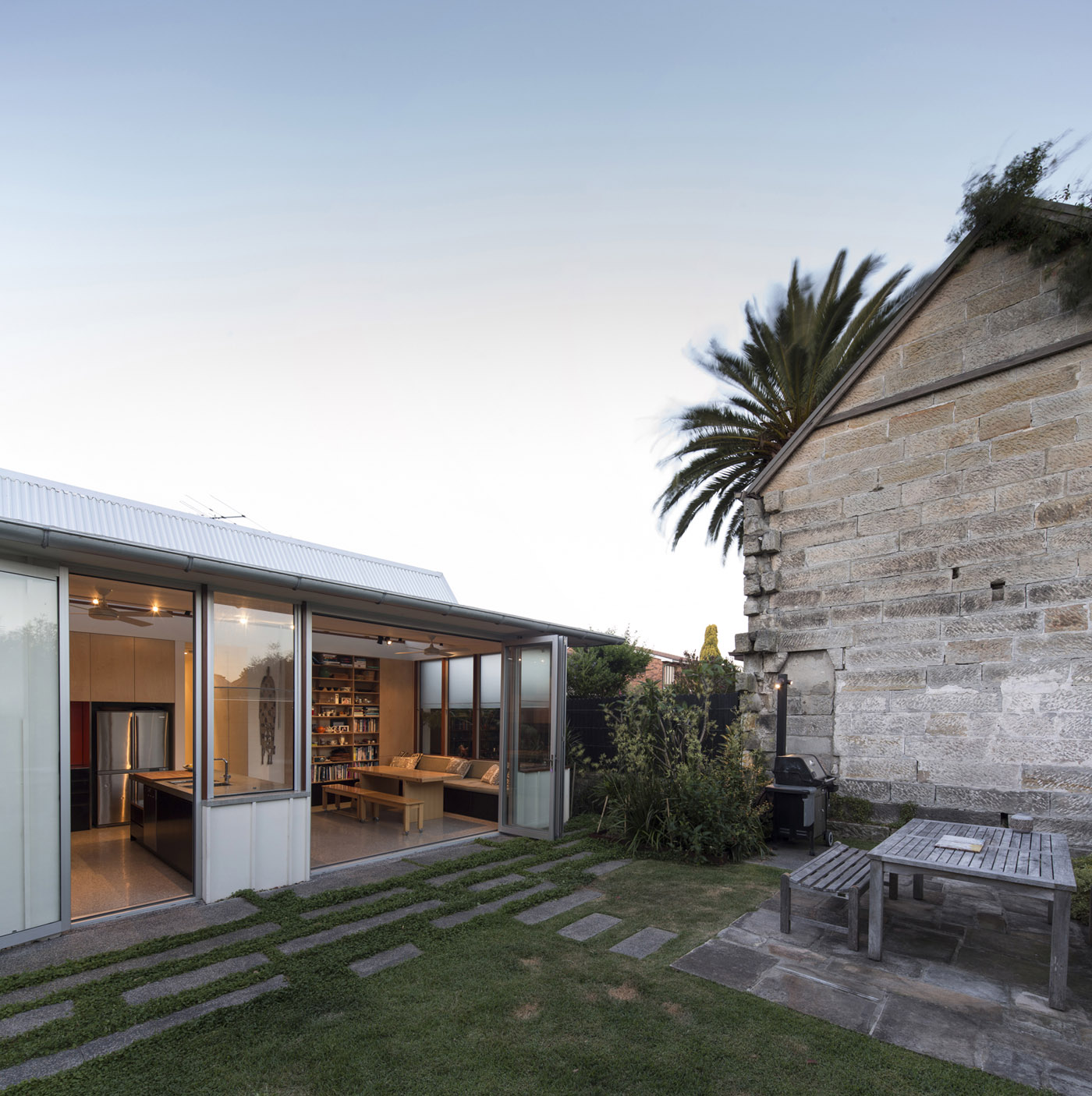 Salgo Kitching House by Sydney award winning architecture office Sam Crawford Architects. Open connection to backyard characterised by existing sandstone wall.