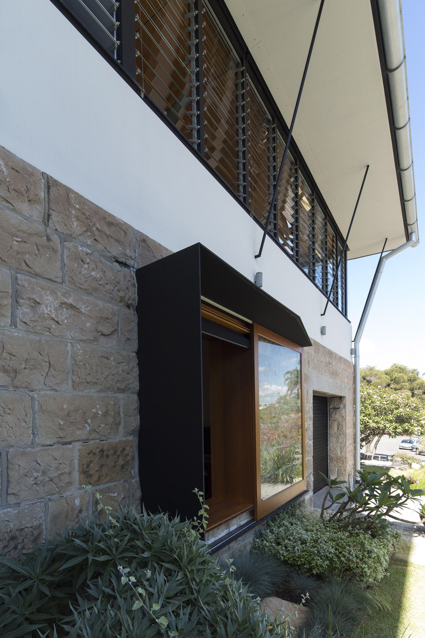 Salgo Kitching House by Sydney award winning architecture office Sam Crawford Architects. Folded steel and large timber windows addition to existing stone wall.
