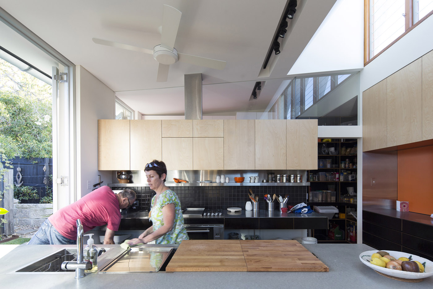 Salgo Kitching House by Sydney award winning architecture office Sam Crawford Architects. Owners preparing food in modern kitchen.