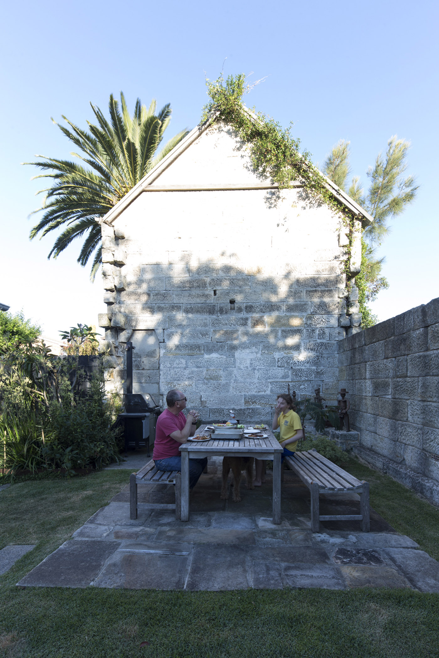 Salgo Kitching House by Sydney award winning architecture office Sam Crawford Architects. Dad and son enjoying outdoor lunch surrounded by heritage stone wall