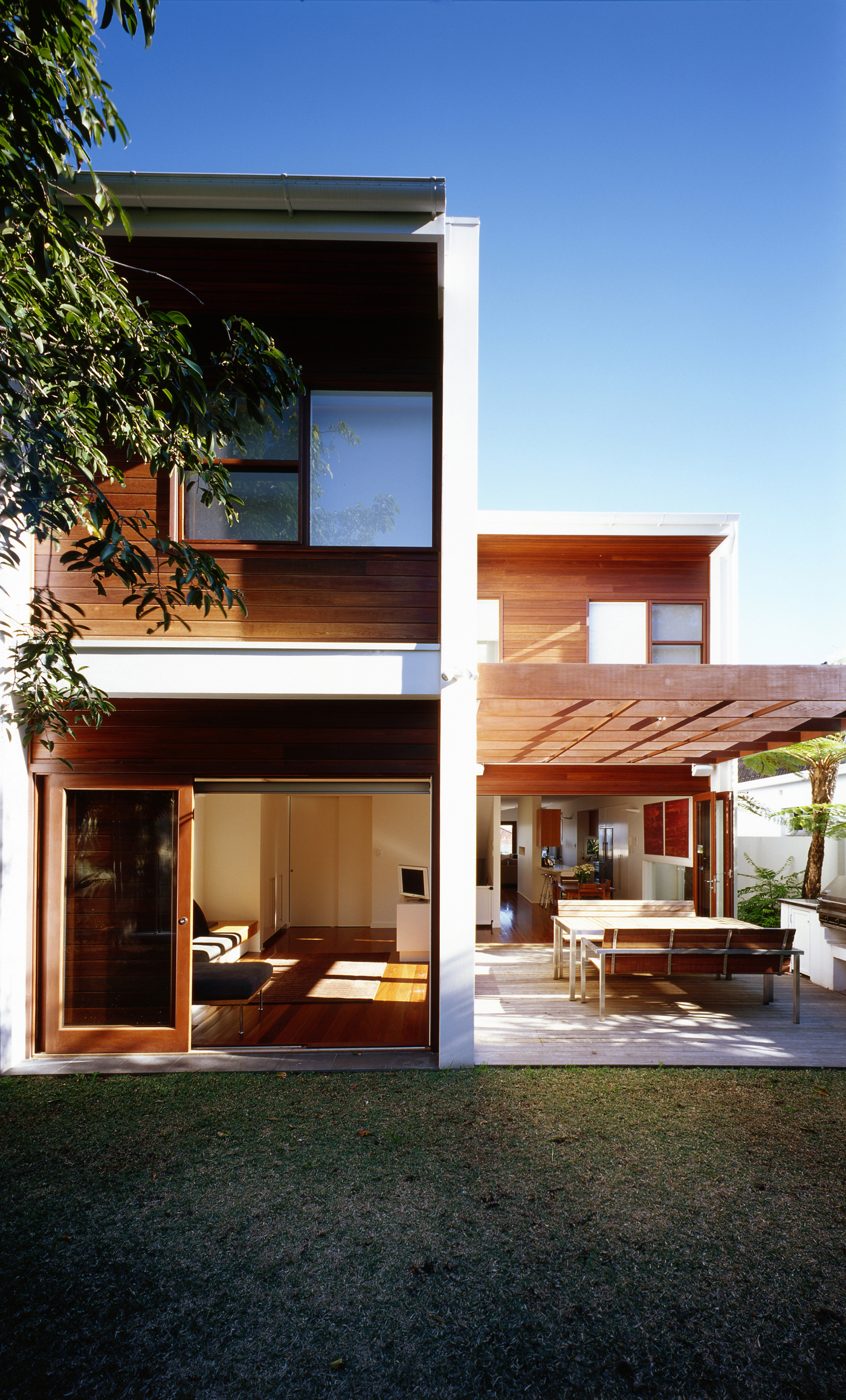 Harbour House by Sydney award winning residential architecture office Sam Crawford Architects. Eastern facade with outdoor terrace connected to backyard