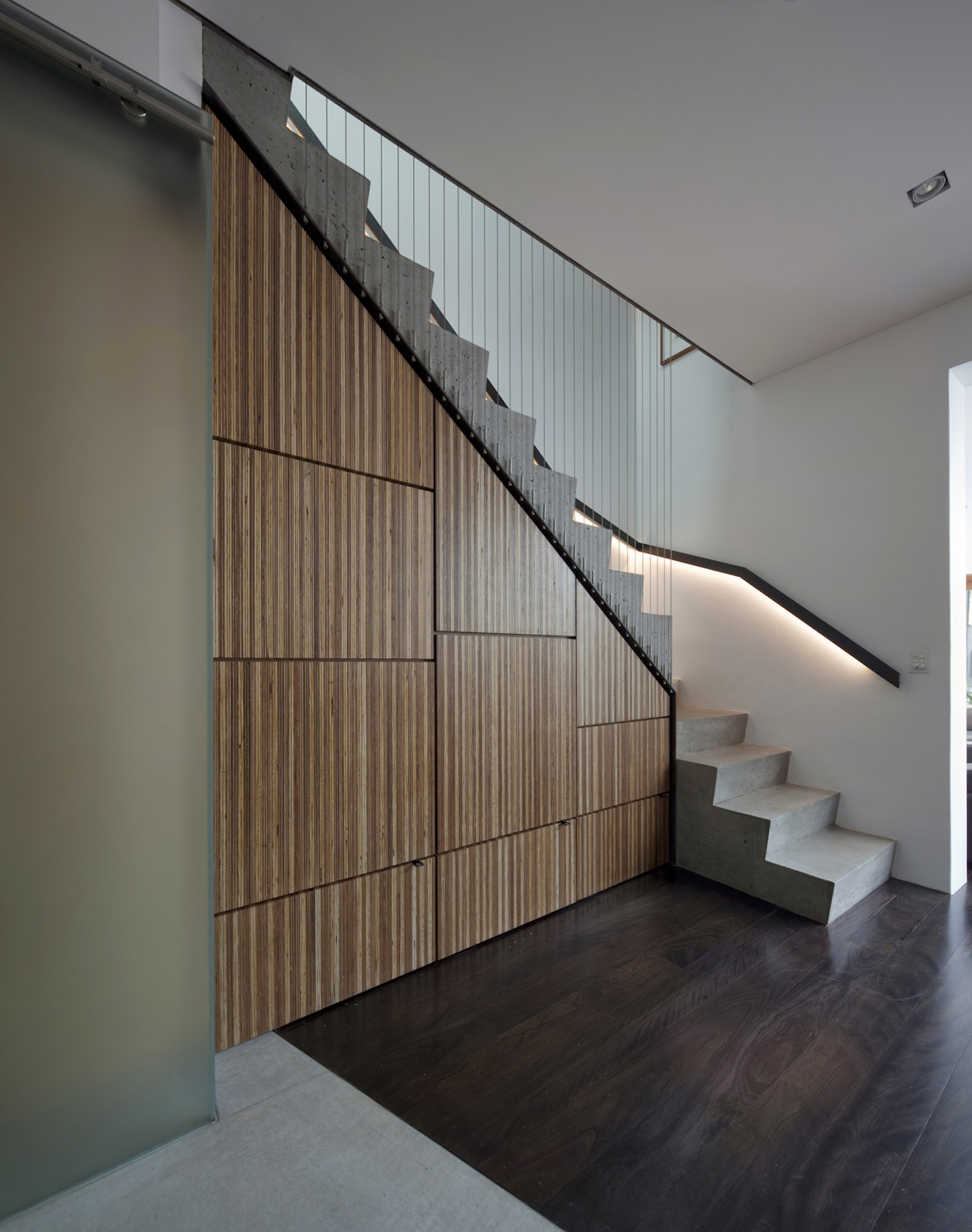 Newtown Terrace by award winning Sydney firm Sam Crawford Architects. Concrete staircase with timber cladded storage underneath