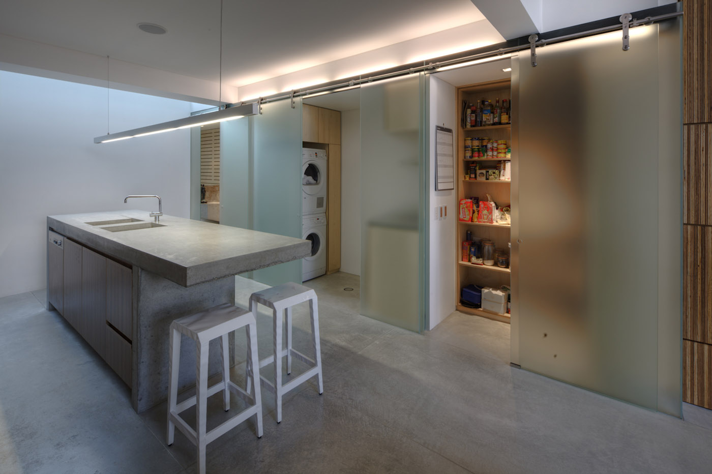 Newtown Terrace by award winning Sydney firm Sam Crawford Architects. Ambient concrete kitchen separated by full height sliding frosted glass panels