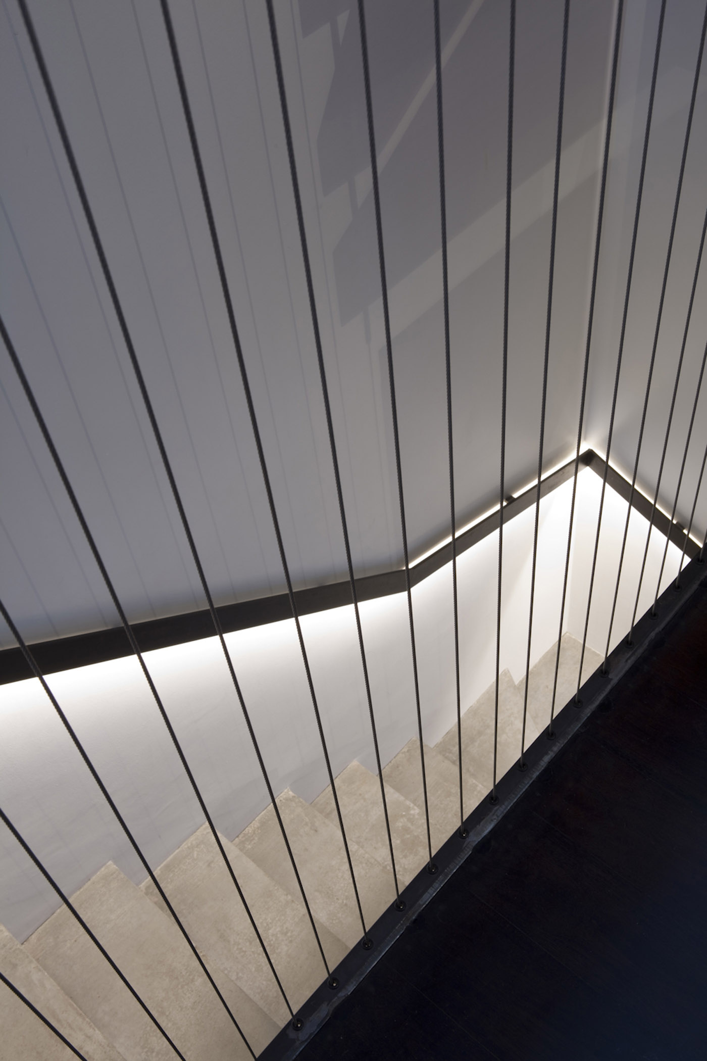 Newtown Terrace by award winning Sydney firm Sam Crawford Architects. View down to backlit flat steel handrail