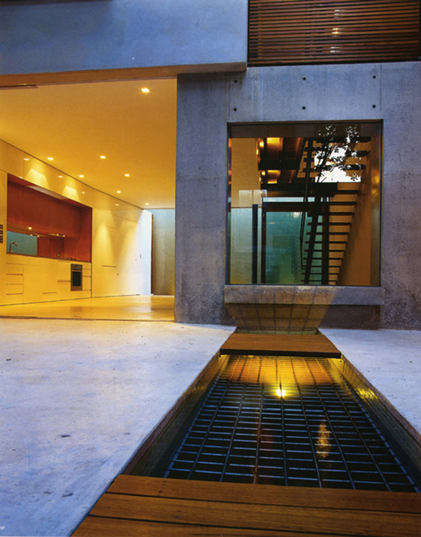 Substation House by award winning residential architecture firm Sam Crawford Architects. View from the ambient concrete courtyard into the open plan kitchen