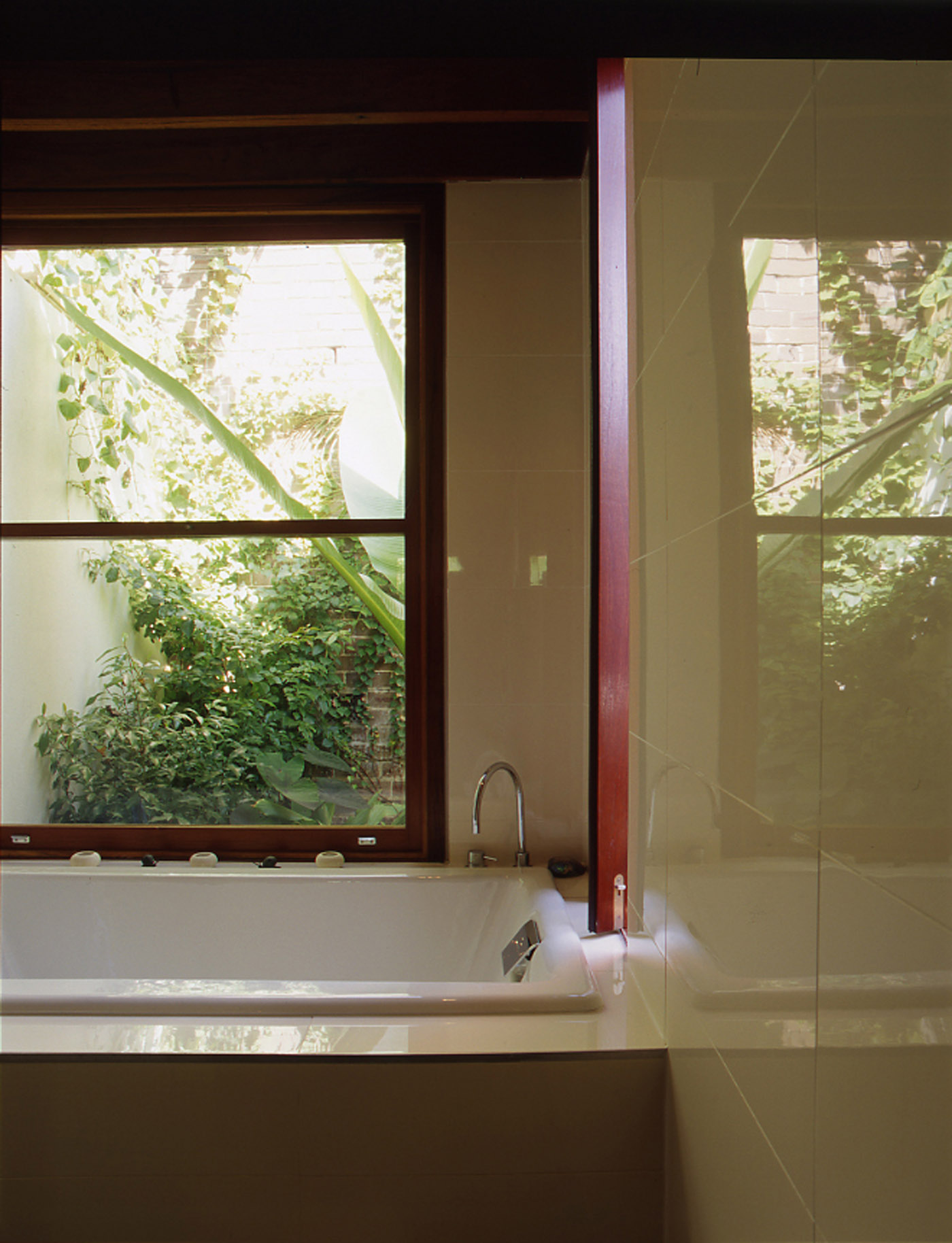 Bandi Drew House by Sydney award winning residential architecture firm Sam Crawford Architects. View from bathroom to green filled courtyard.