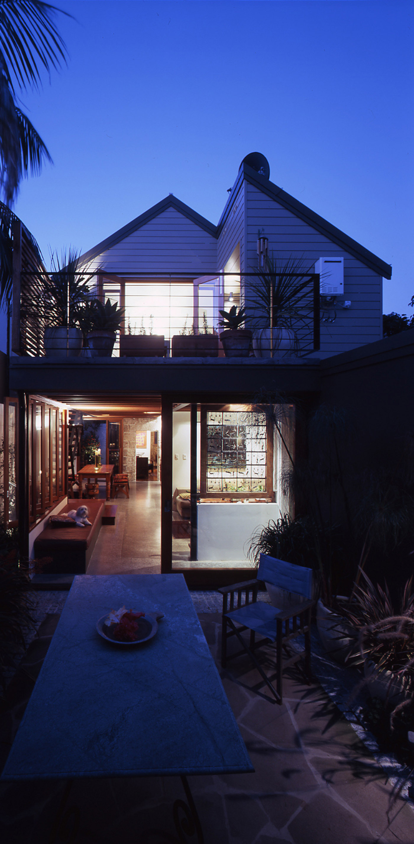 Bandi Drew House by Sydney award winning residential architecture firm Sam Crawford Architects. View from backyard at twilight