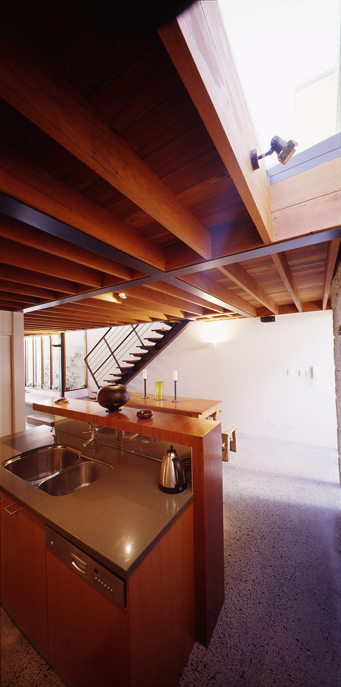 Bandi Drew House by Sydney award winning residential architecture firm Sam Crawford Architects. Exposed ironbark floor joists creates rhythm and provide character to the interior.
