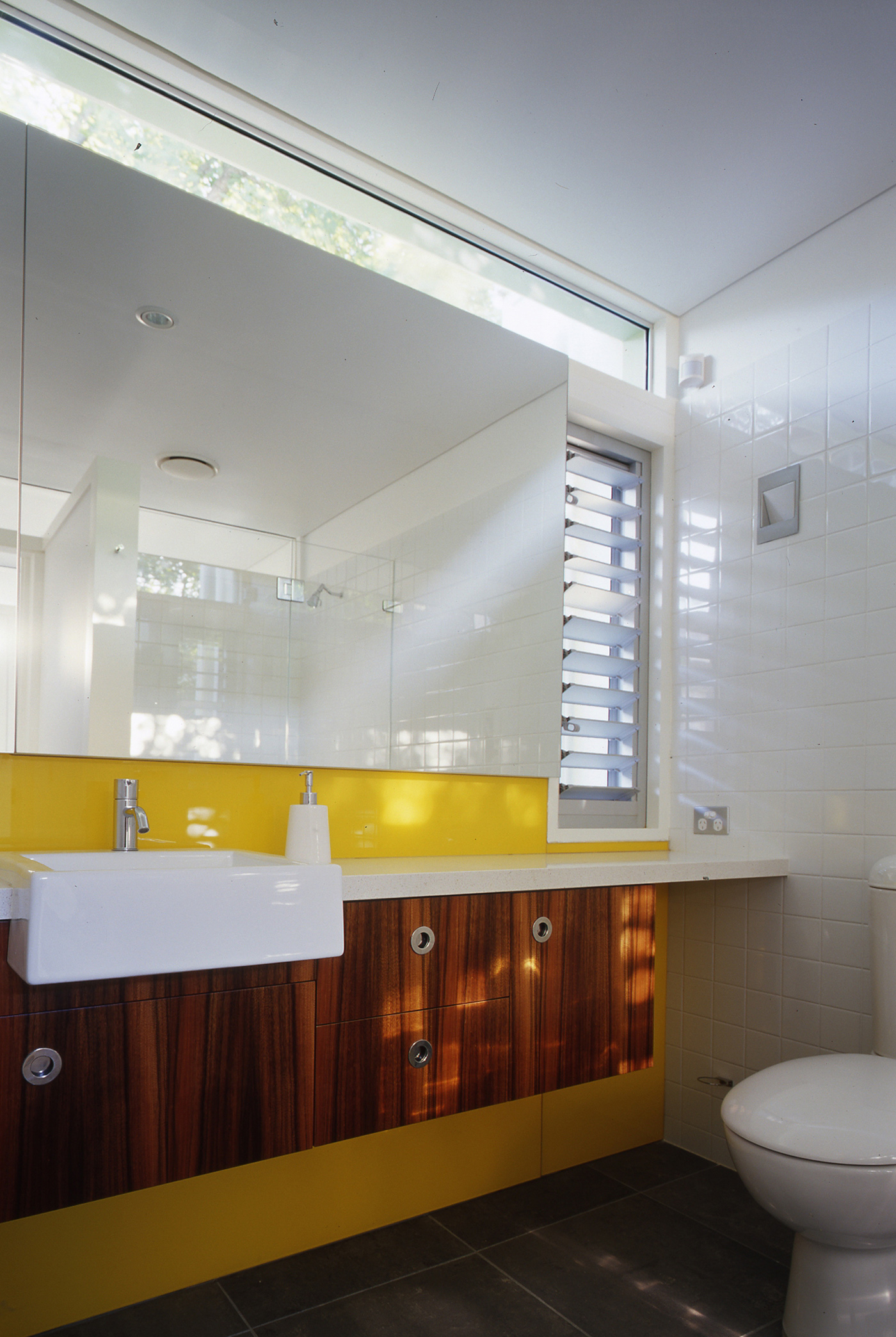 Caristo House by award winning residential architecture office Sam Crawford Architects. Light filled bathroom with yellow splash back, teak joinery and white ceramic tiles