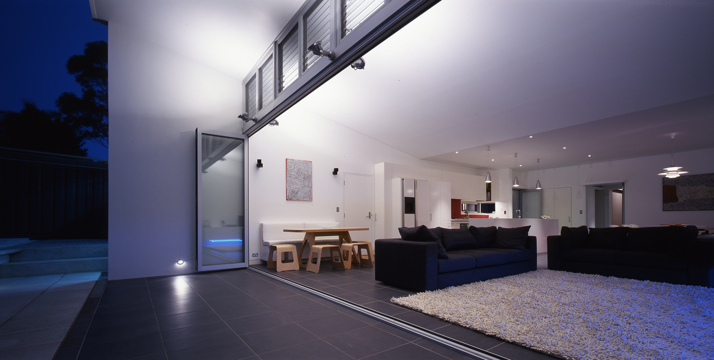Caristo House by award winning residential architecture office Sam Crawford Architects. Night view of the lit up interior