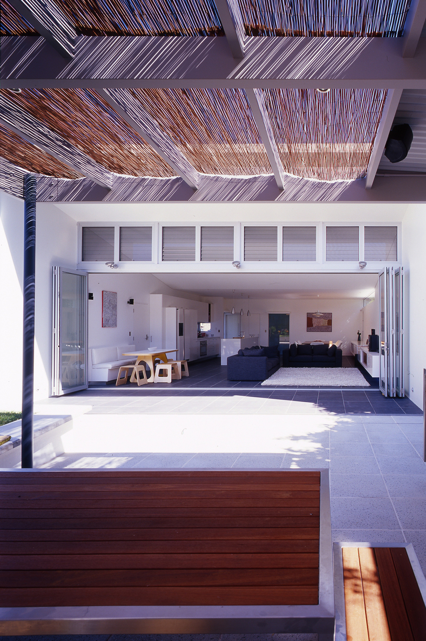 Caristo House by award winning residential architecture office Sam Crawford Architects. Bamboo reed shading to backyard
