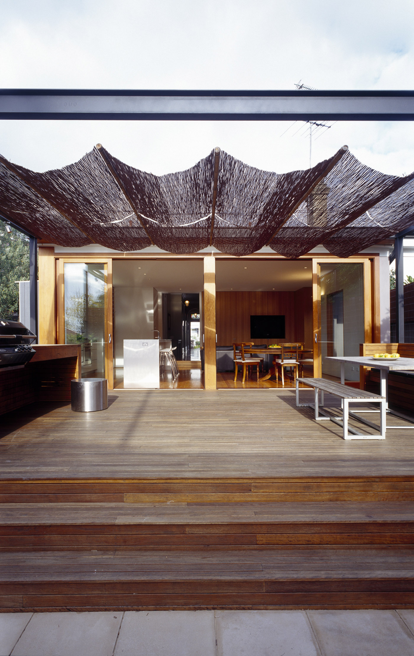 Cooper House by Sydney award winning residential architecture office Sam Crawford Architects. Timber decking with cane reed shading pergola looking into kitchen and dining space