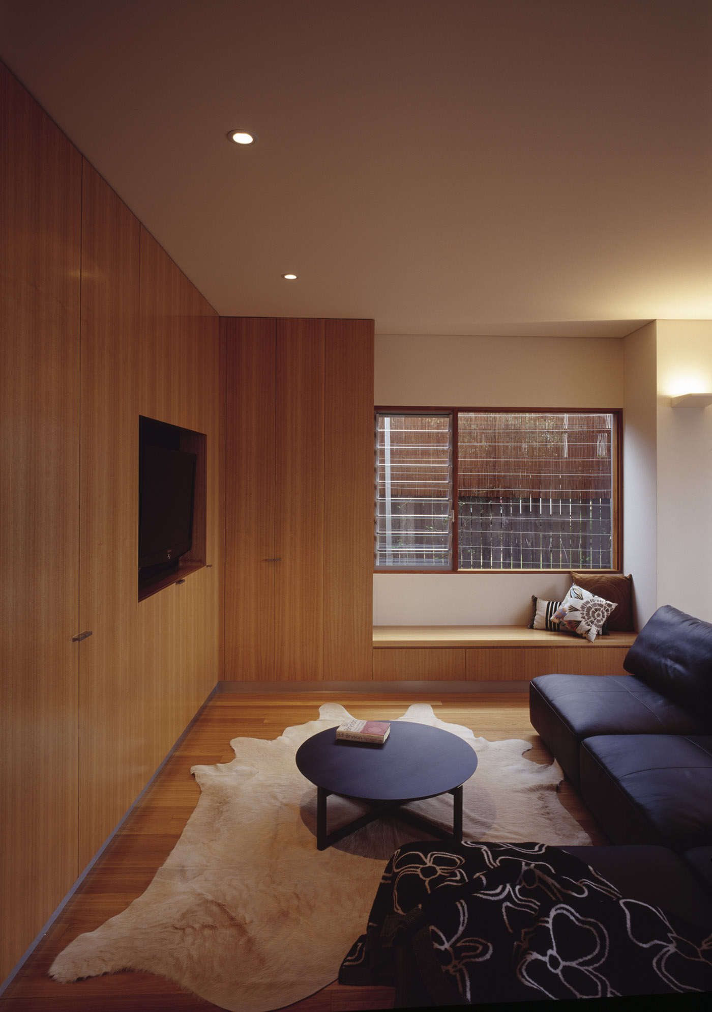 Cooper House by Sydney award winning residential architecture office Sam Crawford Architects. Blackbutt timber joinery and window seat creates ambience to living room.