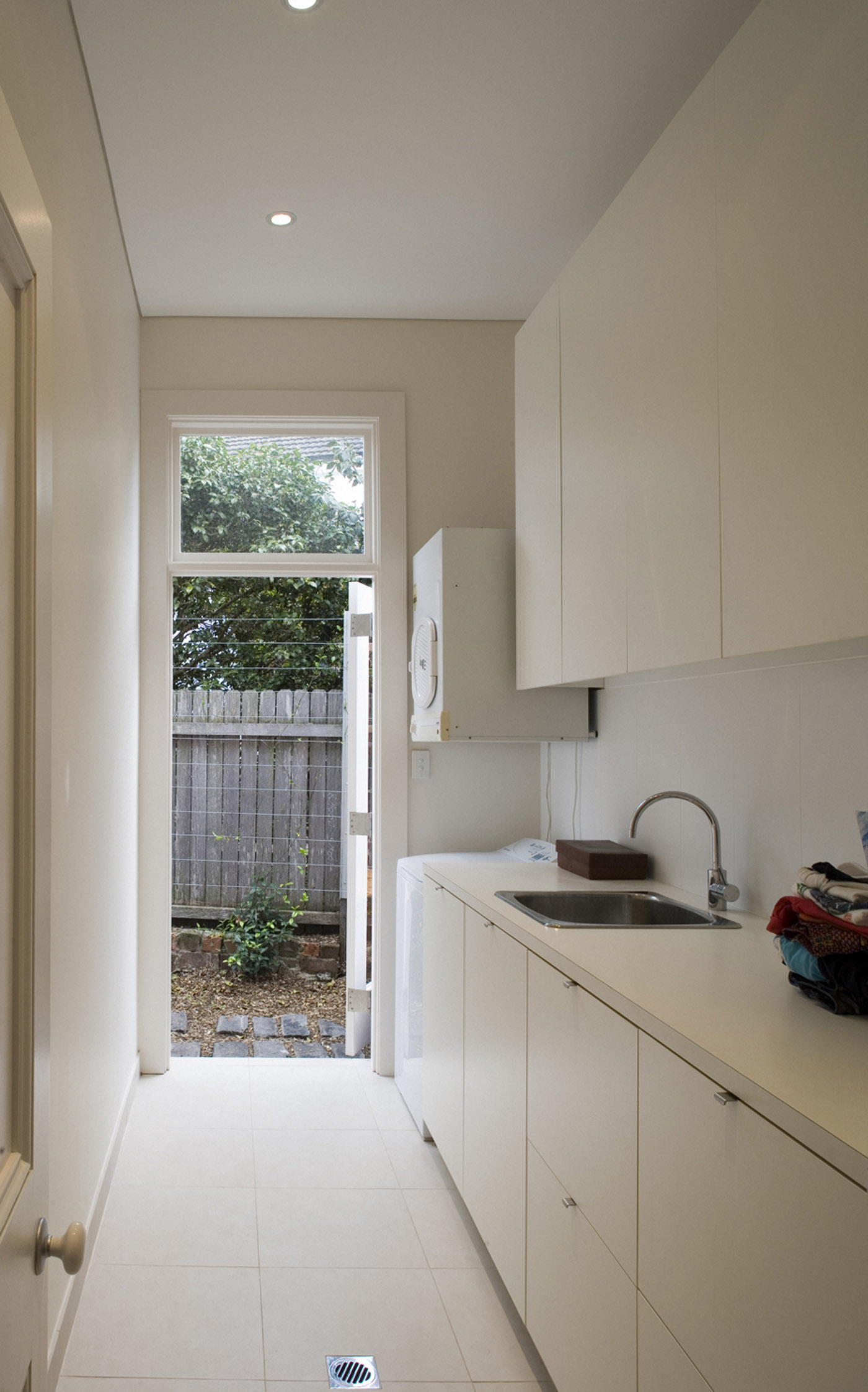 Cooper House by Sydney award winning residential architecture office Sam Crawford Architects. White melamine joinery gives a sense of lightness and brightens narrow laundry space.
