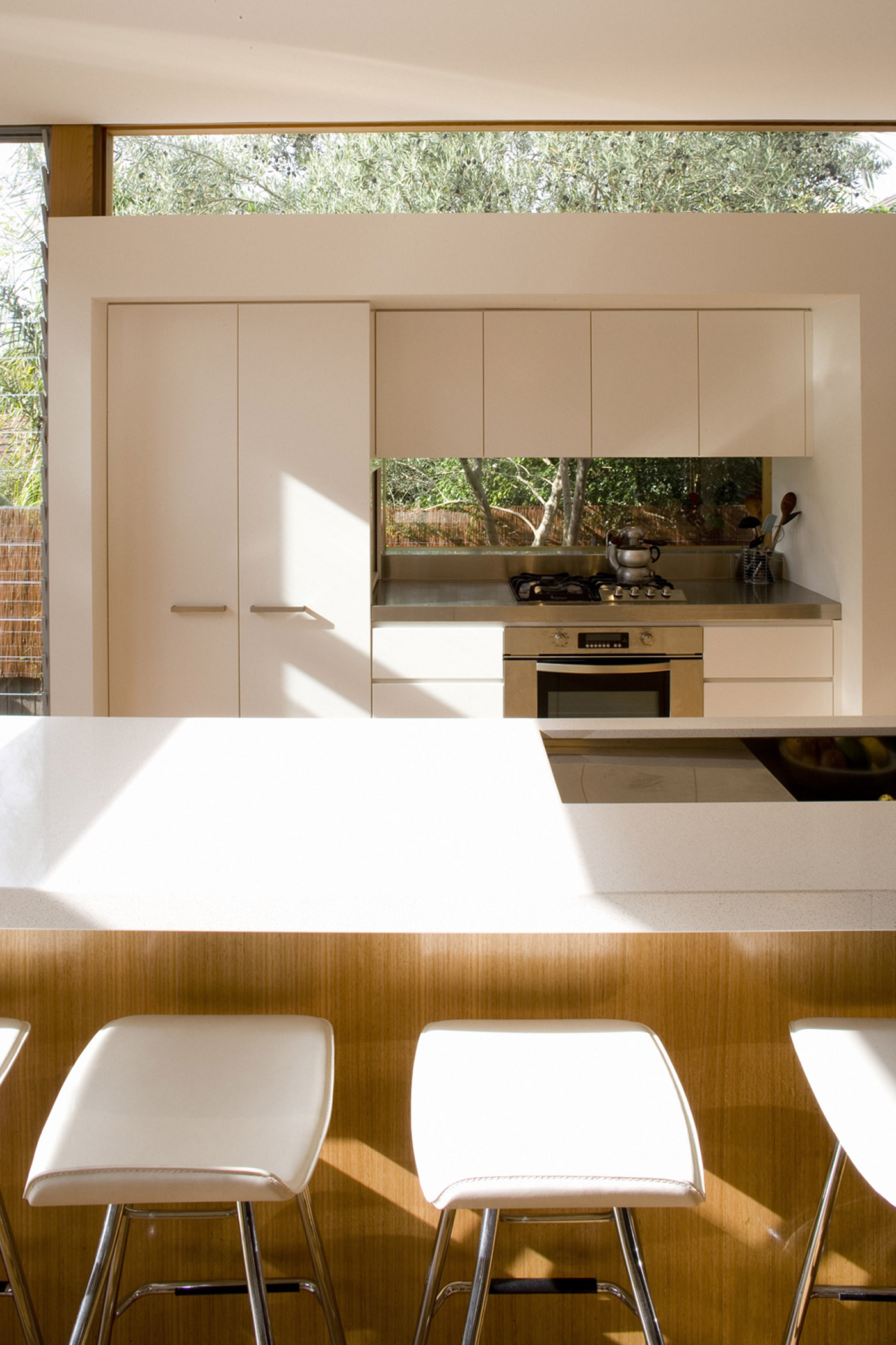 Cooper House by Sydney award winning residential architecture office Sam Crawford Architects. White polyurethane and blackbutt timber joinery with stainless steel benchtop
