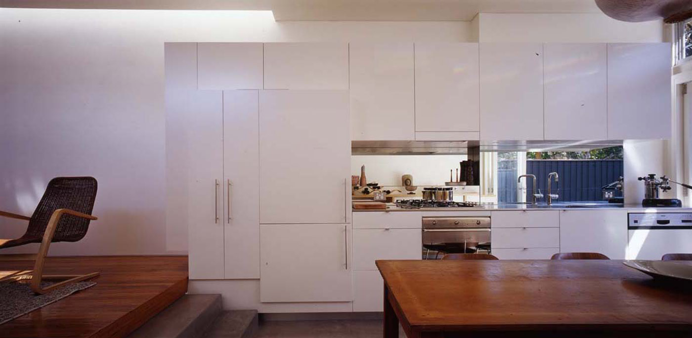 Wake Murphy House by Sydney award winning residential architecture office Sam Crawford Architects. Kitchen unit extends over raised floor.