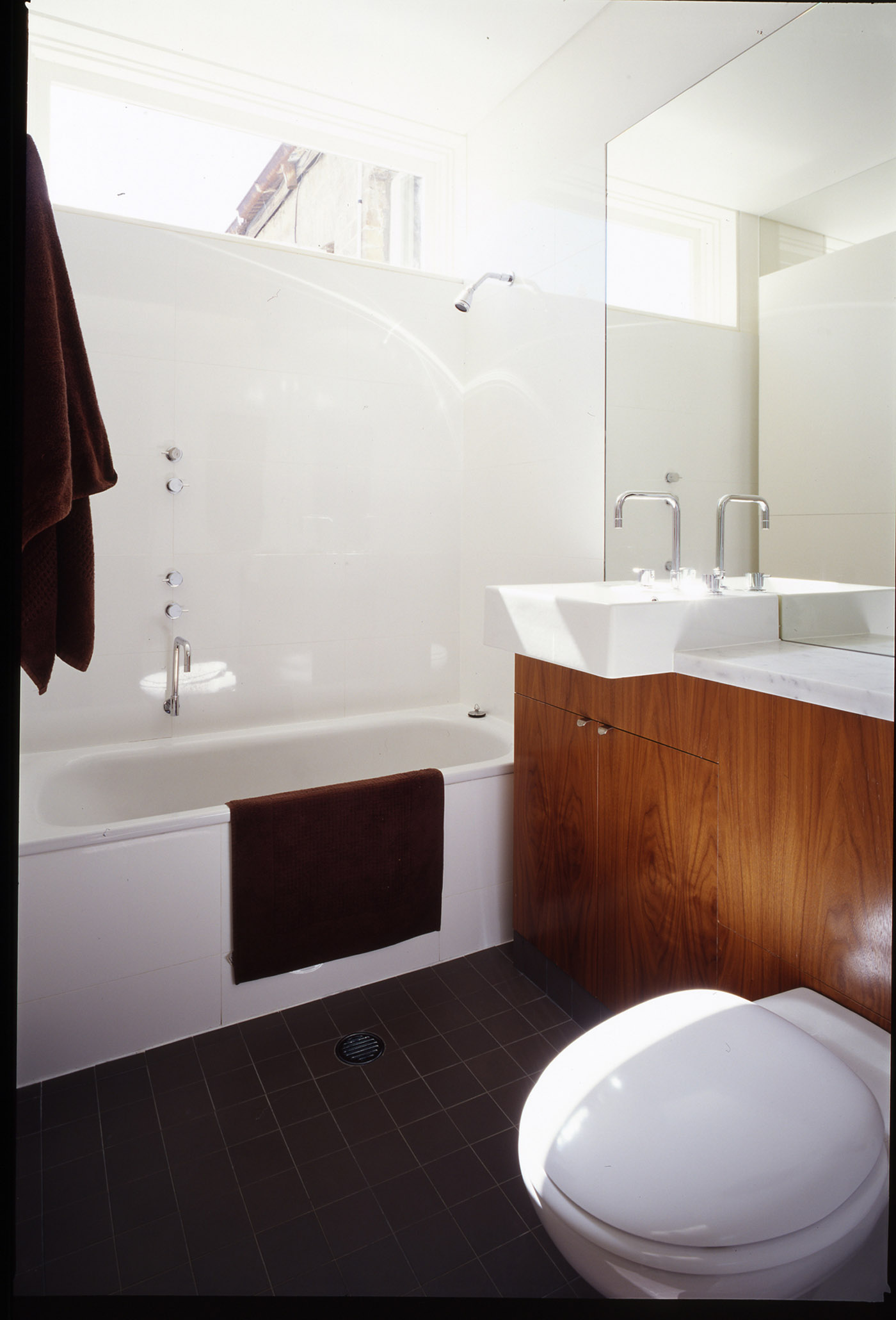 Wake Murphy House by Sydney award winning residential architecture office Sam Crawford Architects. Light filled compact bathroom with timber joinery.
