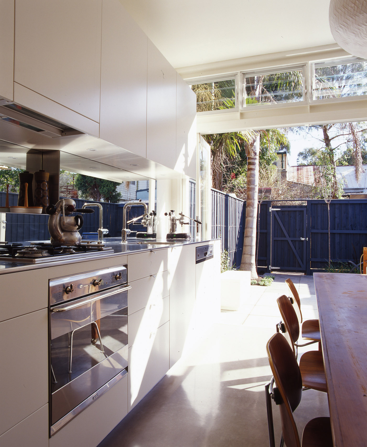 Wake Murphy House by Sydney award winning residential architecture office Sam Crawford Architects. Compact kitchen make use of reflective surfaces