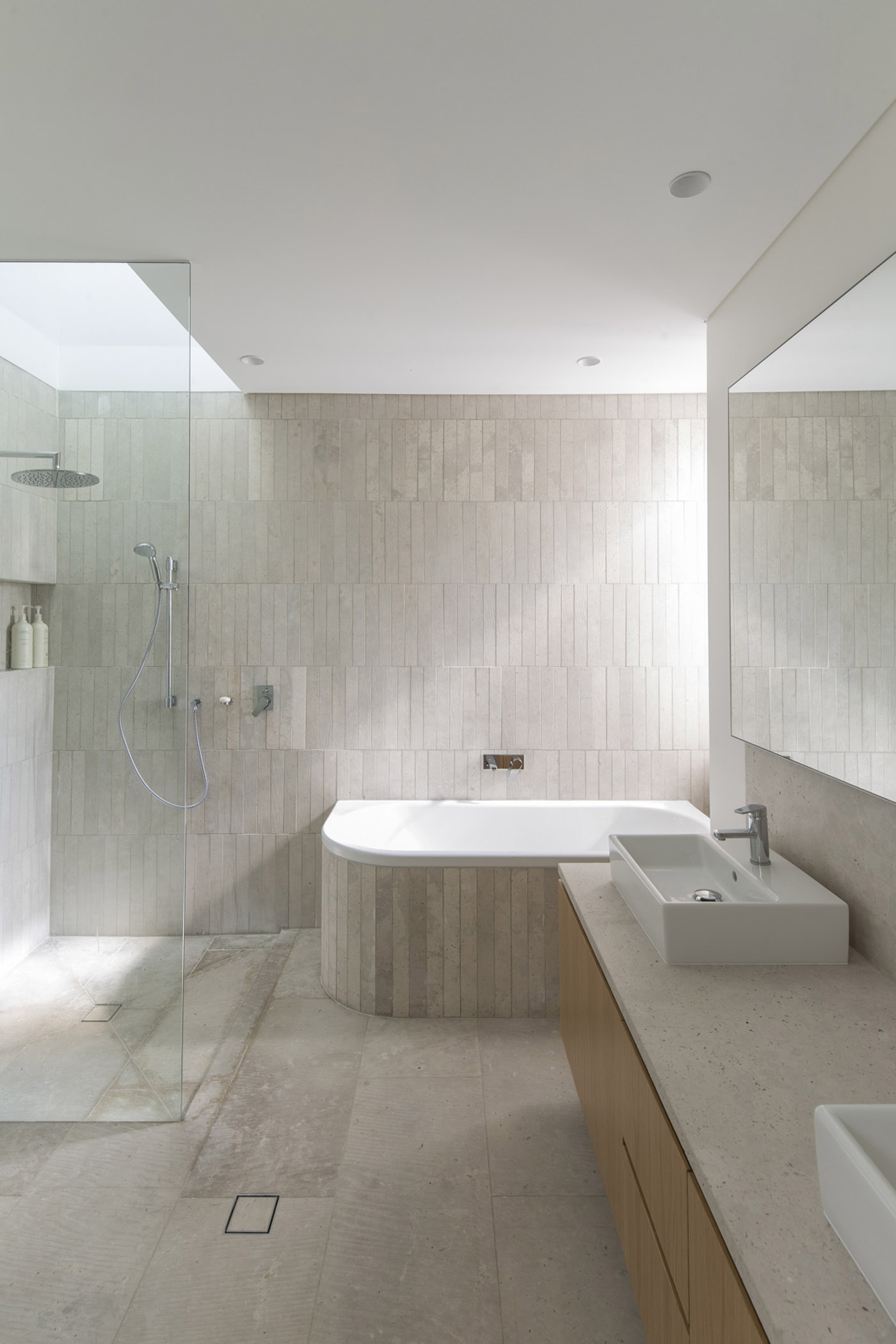 Gandha Kariappa Terrace by Sydney residential architects Sam Crawford Architects. Light filled bathroom with subtle variations of stone tile