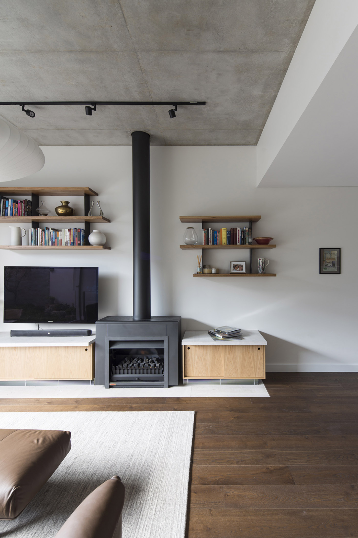 Gandha Kariappa Terrace by Sydney residential architects Sam Crawford Architects. View to living room featuring black fireplace and custom designed joinery