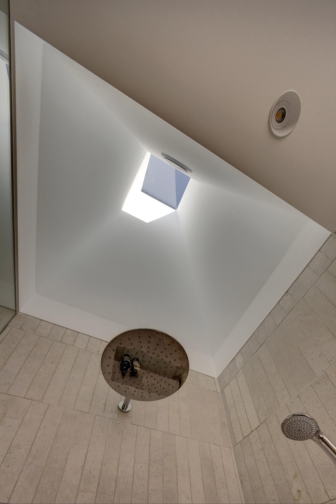 Gandha Kariappa Terrace by Sydney residential architects Sam Crawford Architects. Light filled bathroom with feature skylight above shower