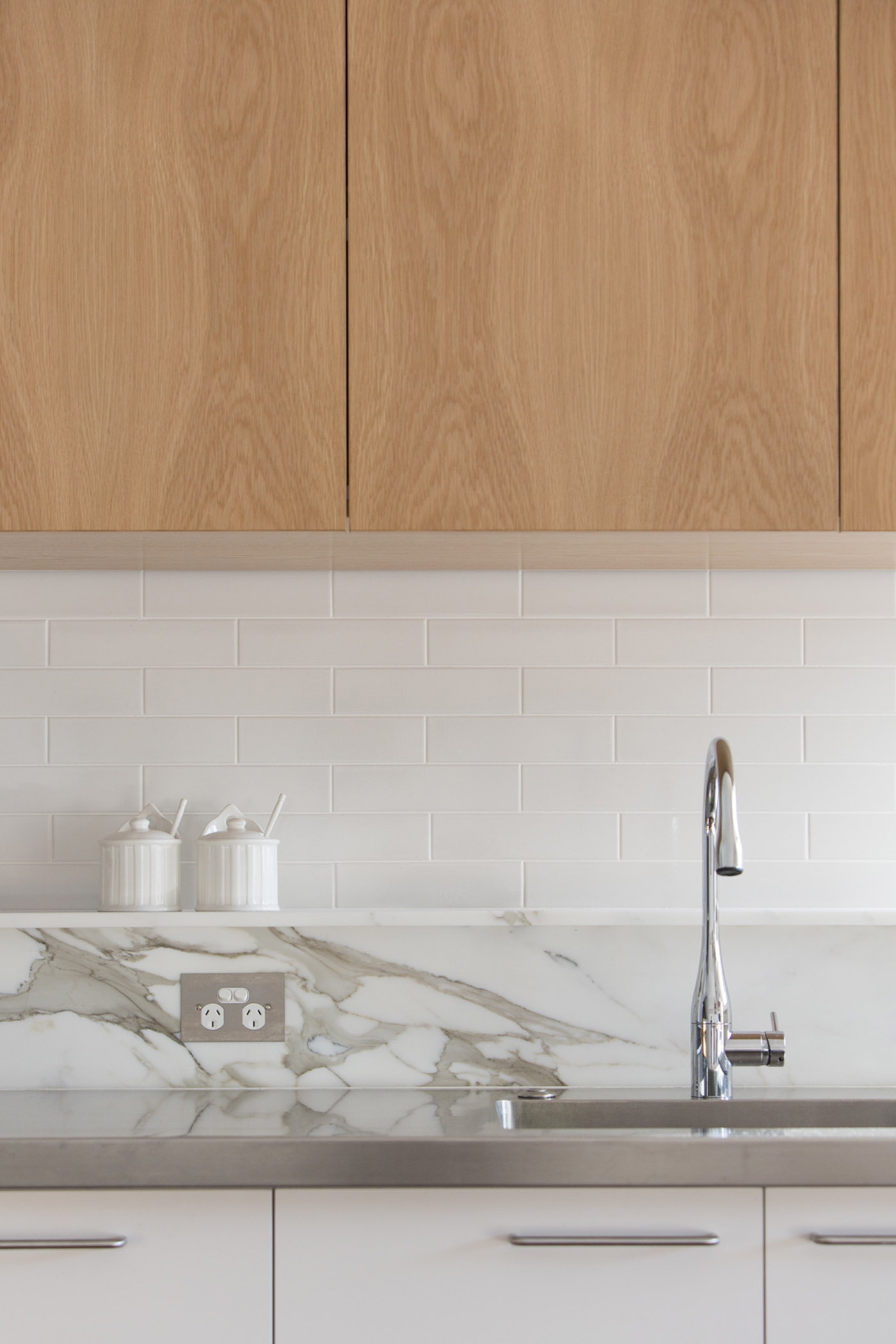 Gandha Kariappa Terrace by Sydney residential architects Sam Crawford Architects. Detail of calacatta marble ledge, stainless steel benchtop, white tiled splashback and white kitchen joinery