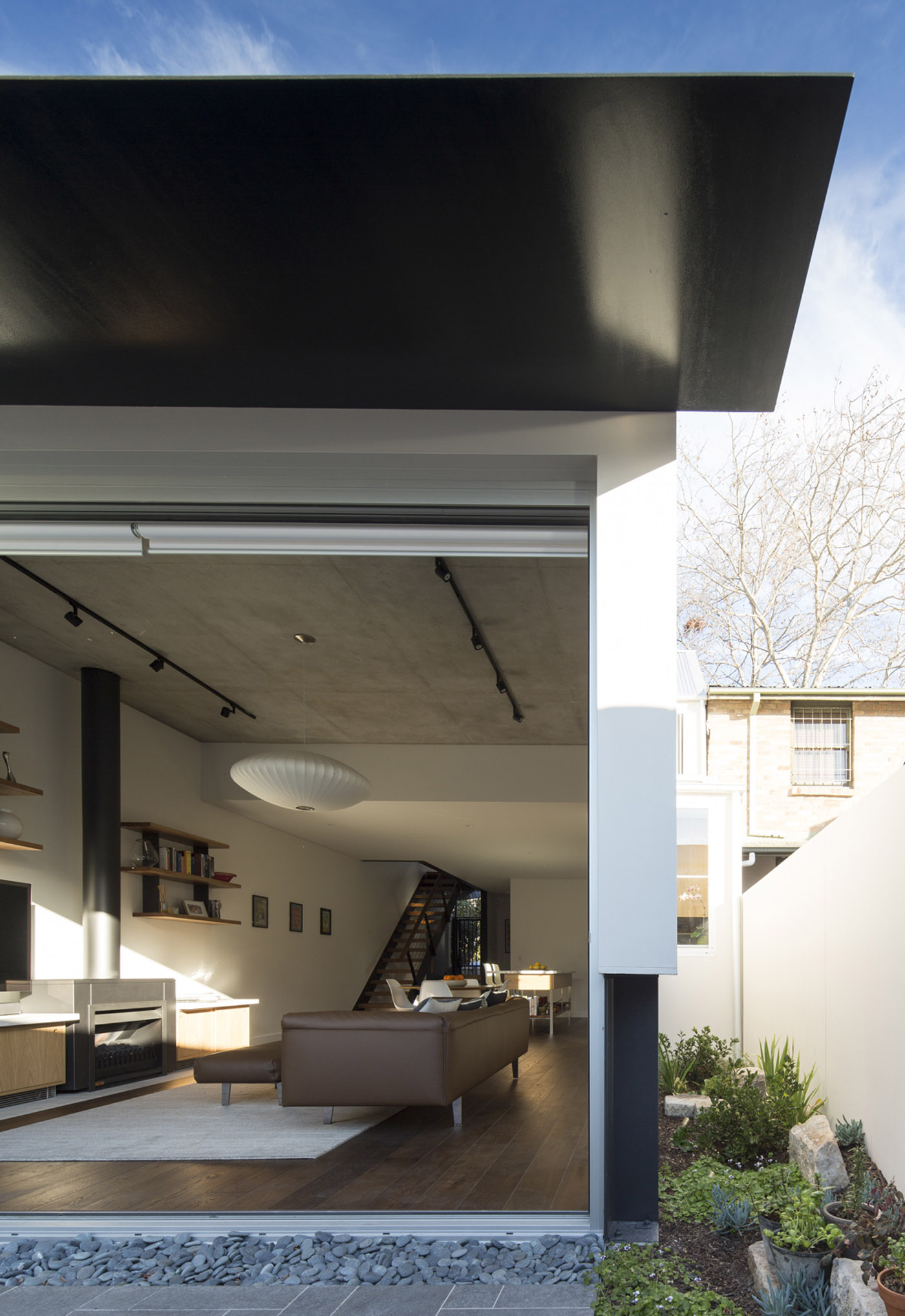 Gandha Kariappa Terrace by Sydney residential architects Sam Crawford Architects. View to ground floor living space from backyard