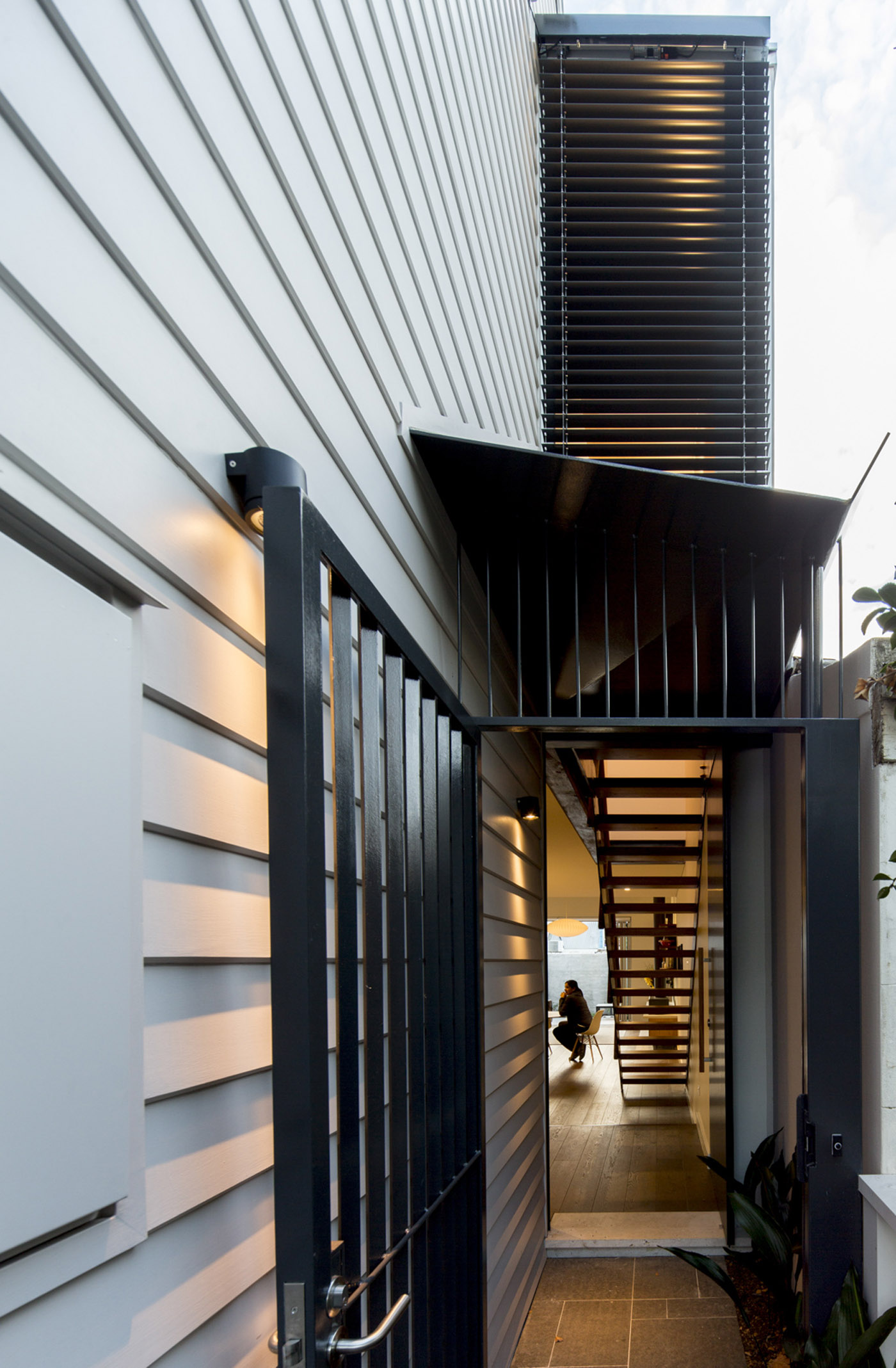 Gandha Kariappa Terrace by Sydney residential architects Sam Crawford Architects. Black powder coated steel side entrance featuring folder steel overhang