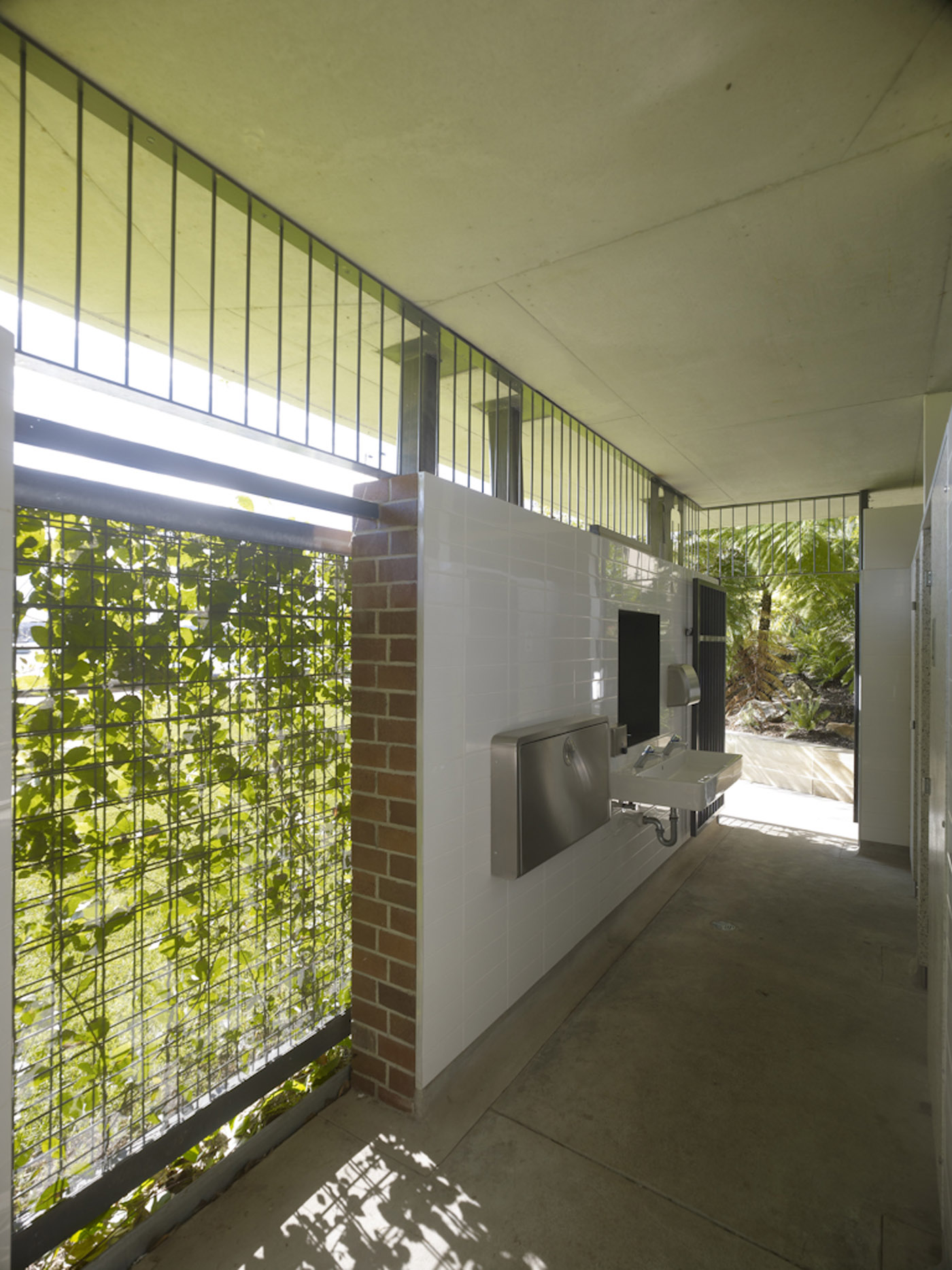 Beare Park Amenities by award winning Sydney public architecture firm Sam Crawford Architects. Green façade filtering light to the interior