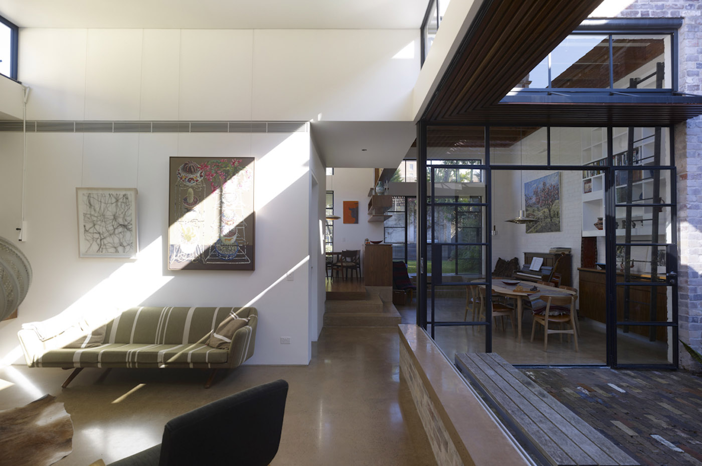 Smee Schoff House by award winning Sydney residential architecture firm Sam Crawford Architects. View to open living space with skylight brings sun to the interior