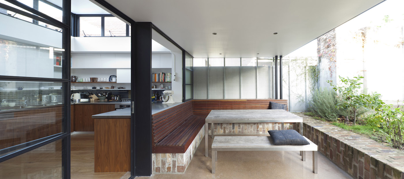 Smee Schoff House by award winning Sydney residential architecture firm Sam Crawford Architects. Kitchen and outdoor sitting space connected by transparent glass openings