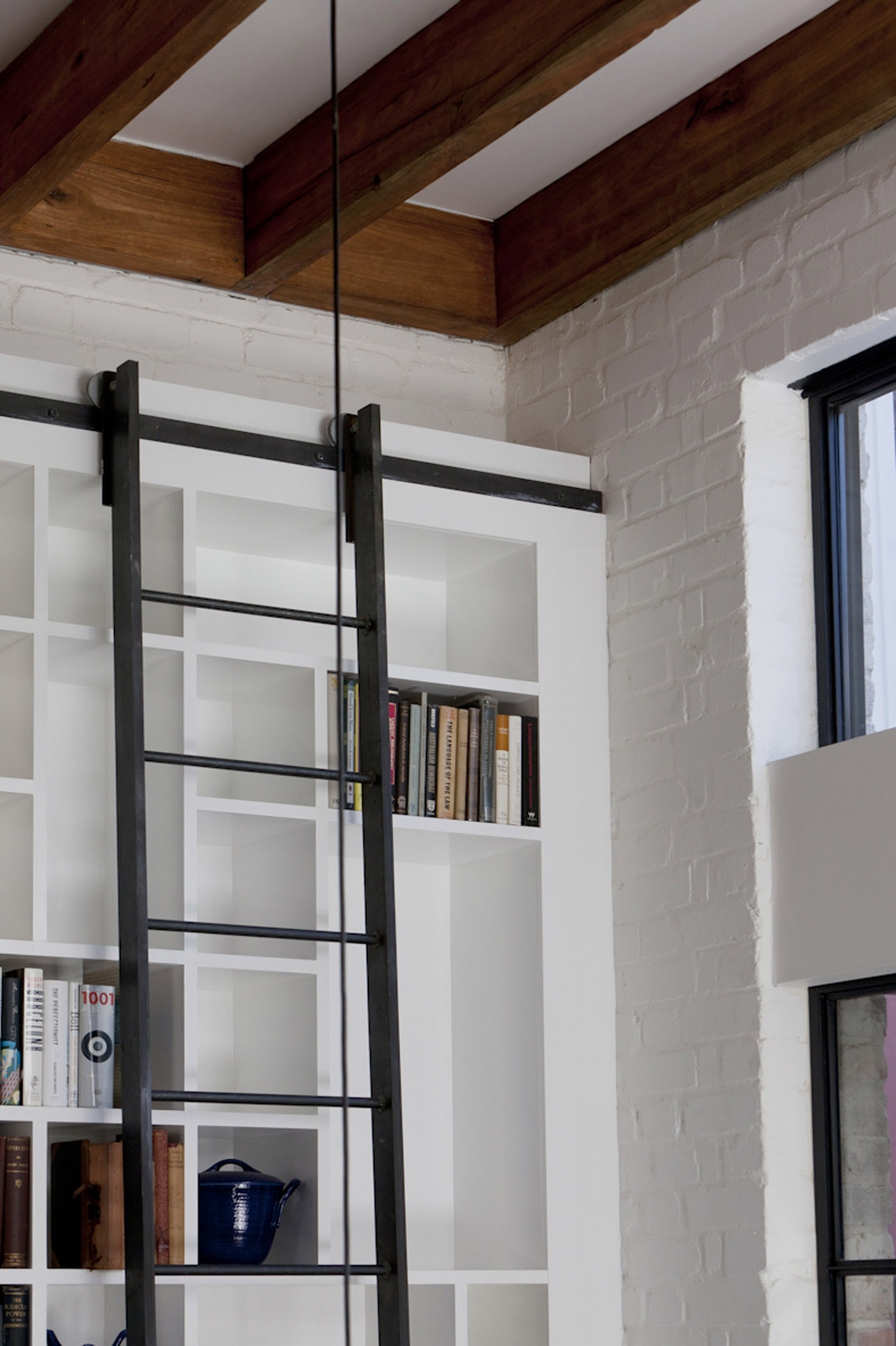 Smee Schoff House by award winning Sydney residential architecture firm Sam Crawford Architects. Detail of movable ladder on double-height bookcase